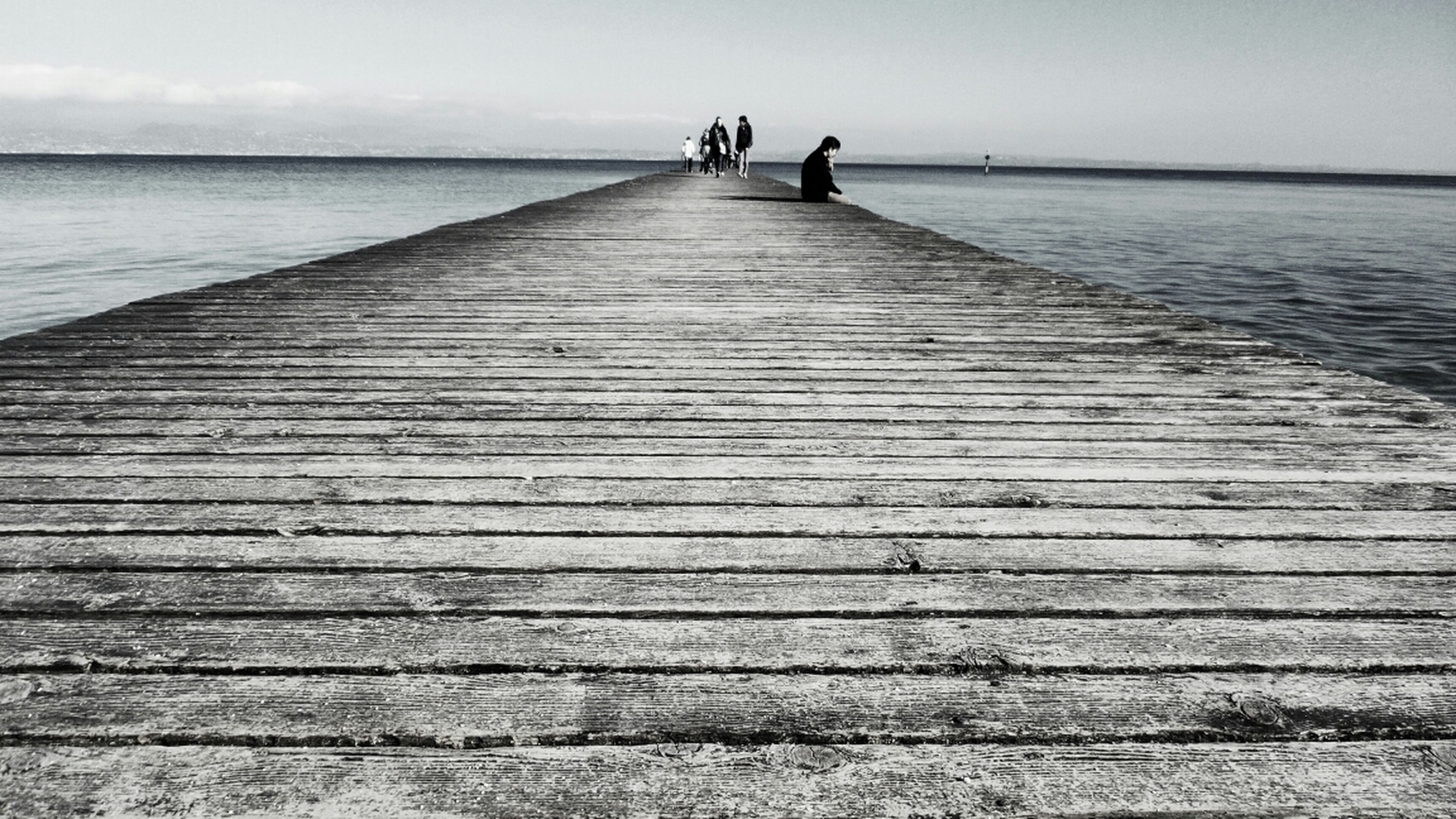 water, sea, pier, lifestyles, leisure activity, men, tranquil scene, tranquility, horizon over water, wood - material, jetty, rear view, scenics, person, nature, boardwalk, beauty in nature