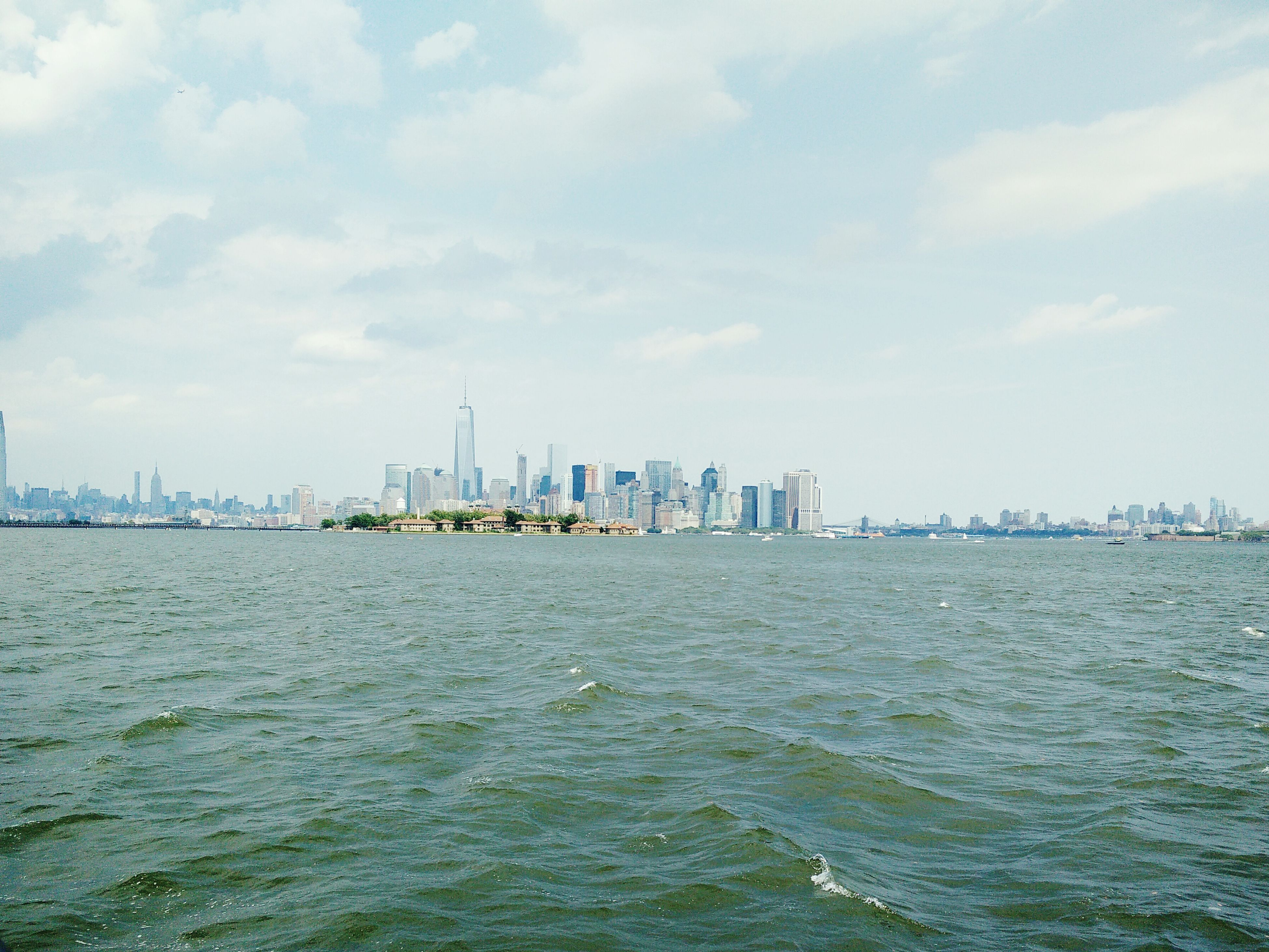 water, building exterior, architecture, waterfront, built structure, city, sea, sky, cityscape, skyscraper, urban skyline, river, tower, tall - high, rippled, cloud - sky, cloud, skyline, mid distance, day