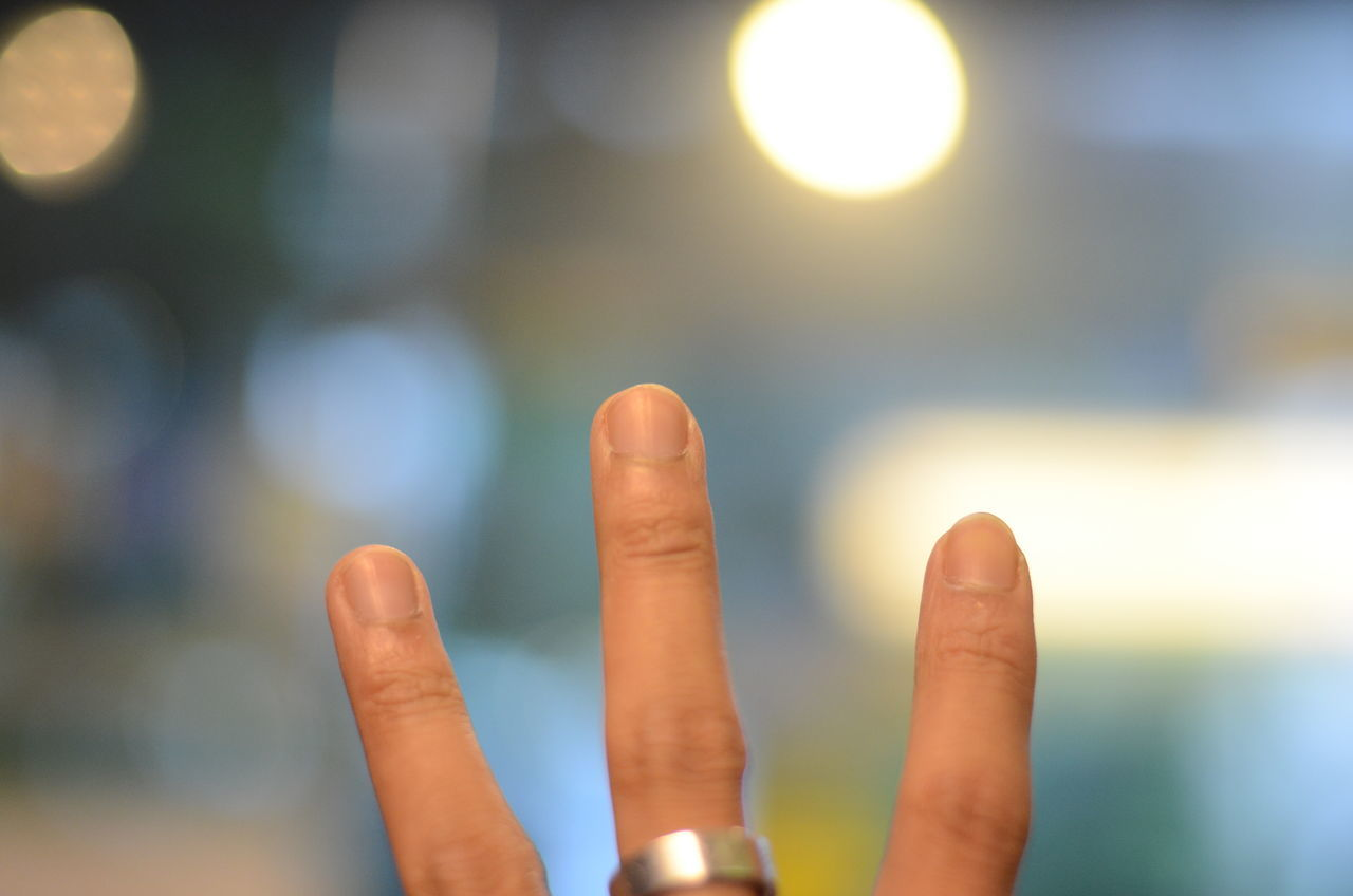 human finger, focus on foreground, human hand, human body part, gesturing, outdoors, real people, communication, close-up, one person, day, people