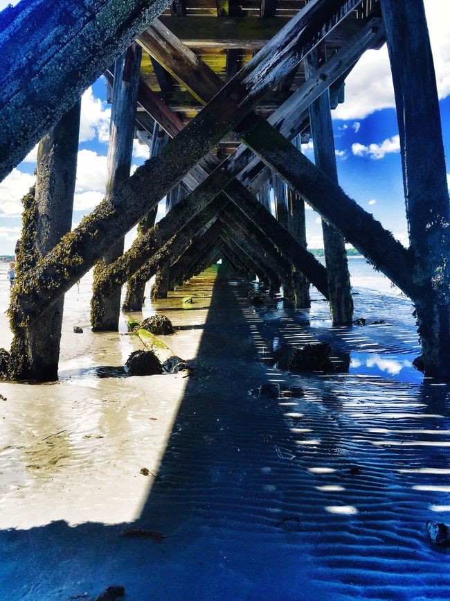 Under the wooden pier at fort Foster beach in Kittery, ME surrounded by the Sandy beach, the reflections of sunlight and the bright blue sky Summer Sunlight Daylight Wooden Pier At Ocean East Coast Blue Skies White Clouds