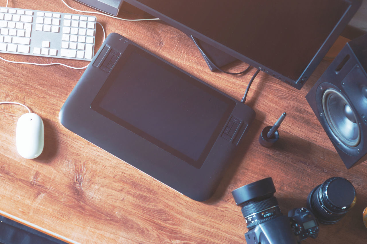 High Angle View Of Graphics Tablet With Camera On Desk