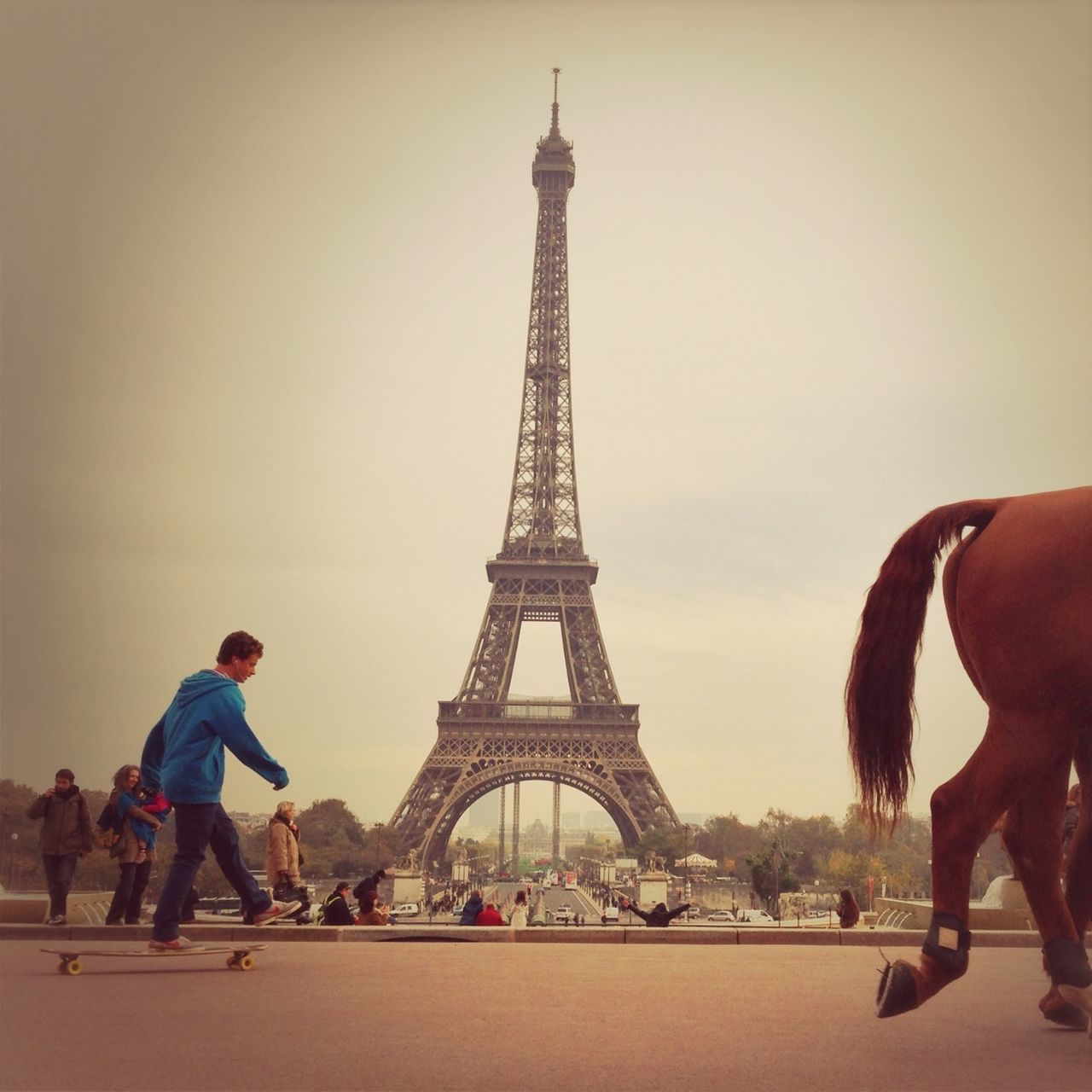 eiffel tower, tower, tourism, international landmark, travel destinations, culture, famous place, travel, architecture, built structure, full length, capital cities, tall - high, city, tourist, casual clothing, in front of, iron - metal, building exterior, sky, vacations, tall, history, day, architectural feature, outdoors