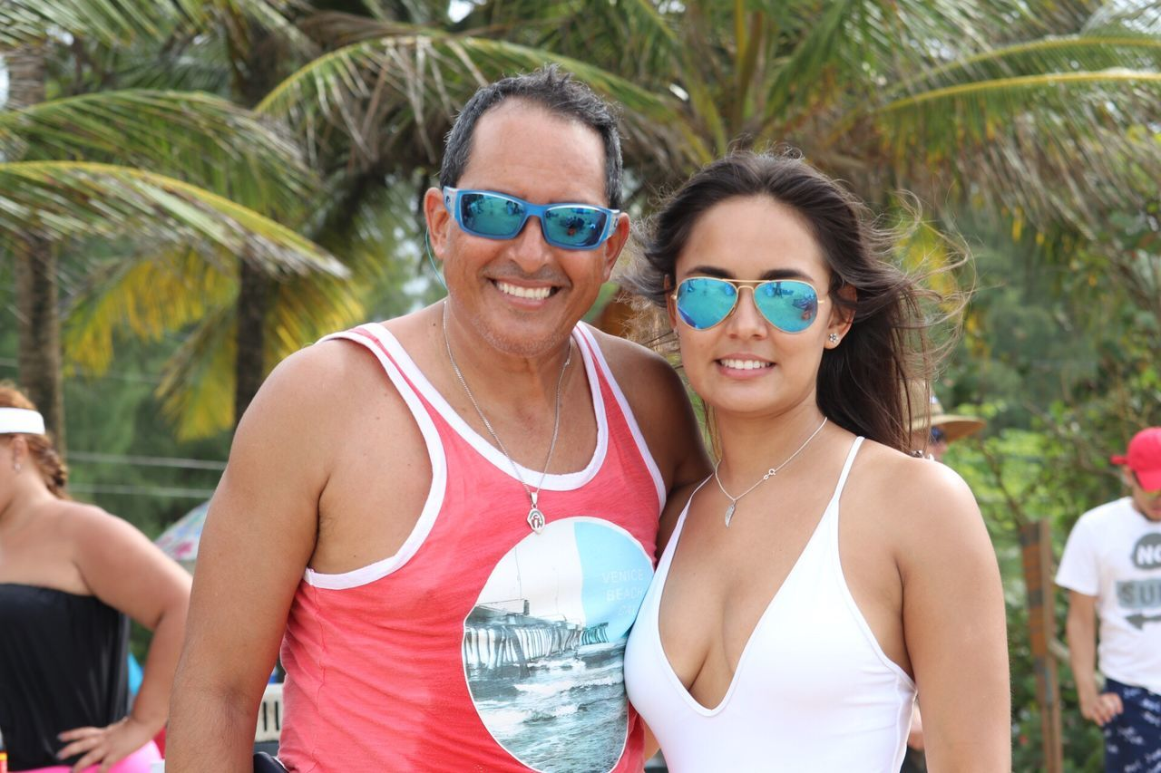 Portrait Of Mature Man And Young Woman Wearing Sunglasses While Standing At Beach