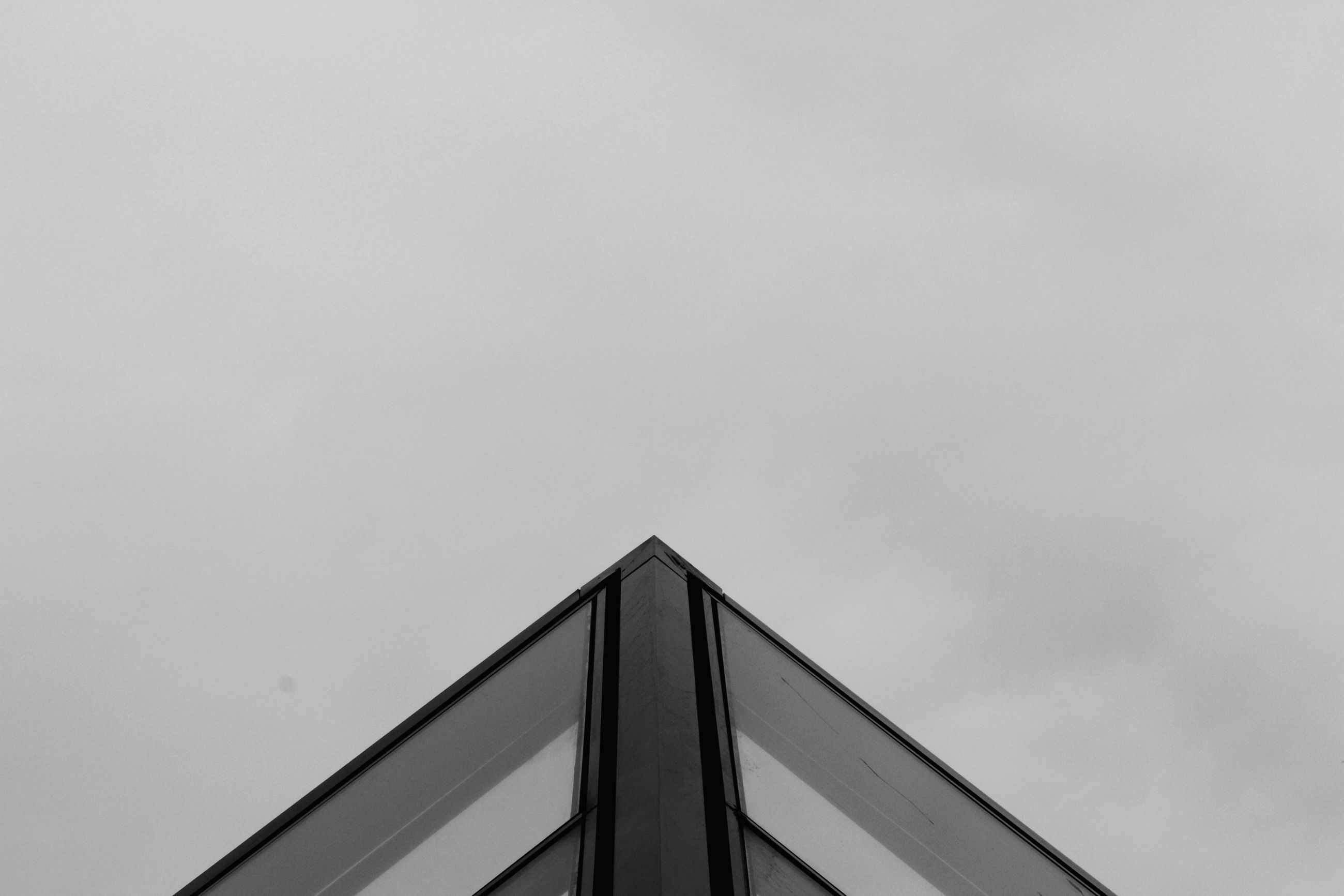 architecture, low angle view, built structure, building exterior, copy space, clear sky, high section, sky, building, outdoors, day, no people, city, modern, part of, overcast, window, office building, roof, residential structure