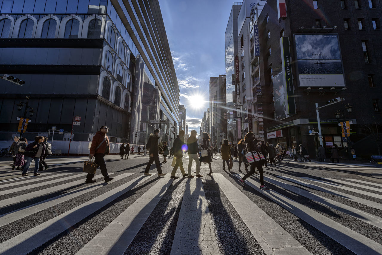 building exterior, architecture, built structure, large group of people, city, walking, street, sunlight, city life, outdoors, day, men, sky, real people, people, adult