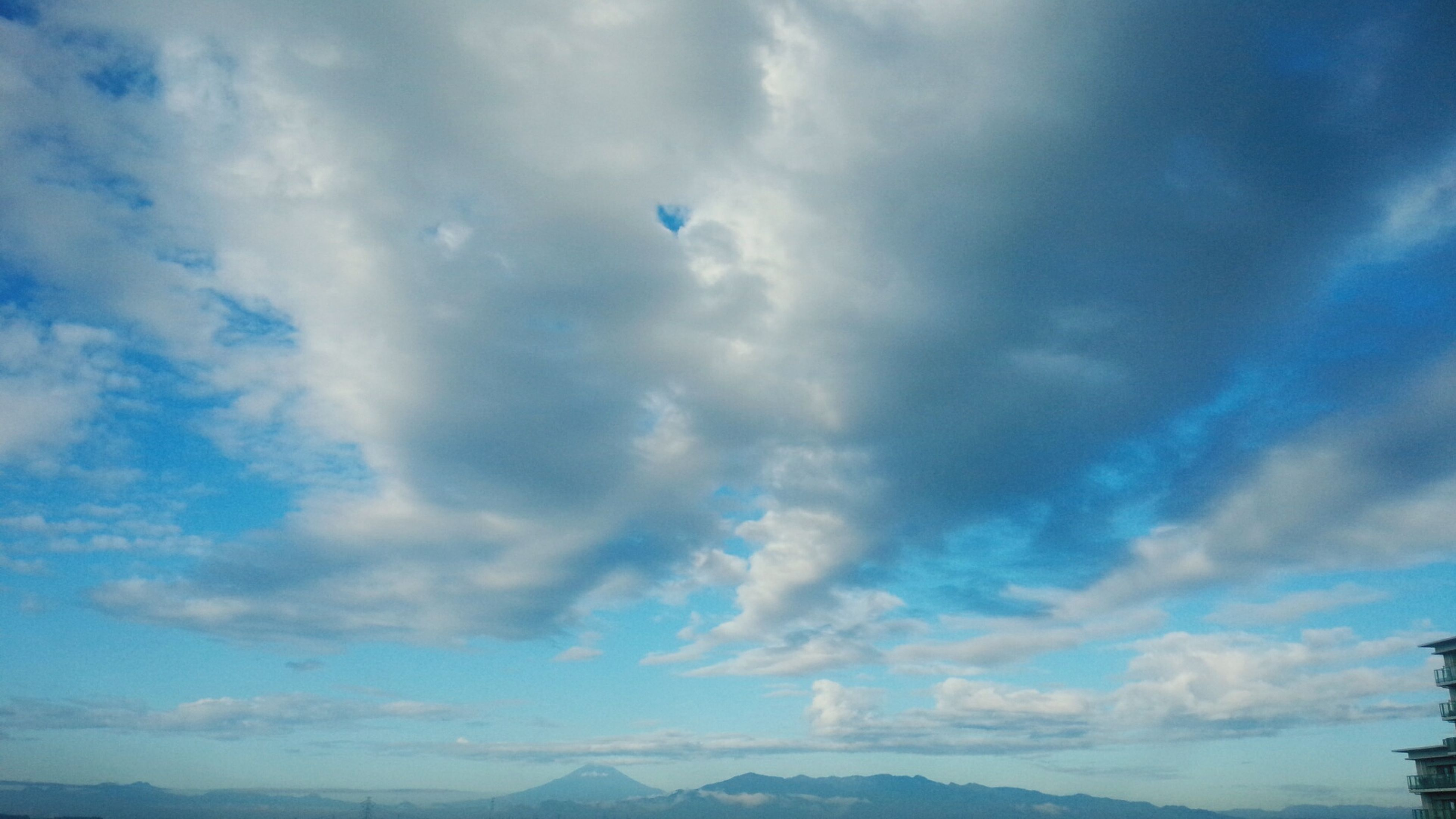 sky, tranquil scene, landscape, tranquility, scenics, cloud - sky, beauty in nature, mountain, nature, cloud, flying, non-urban scene, cloudy, blue, mountain range, outdoors, day, majestic, remote, no people, physical geography, solitude, cloudscape, fluffy, atmospheric mood, countryside, horizon over land