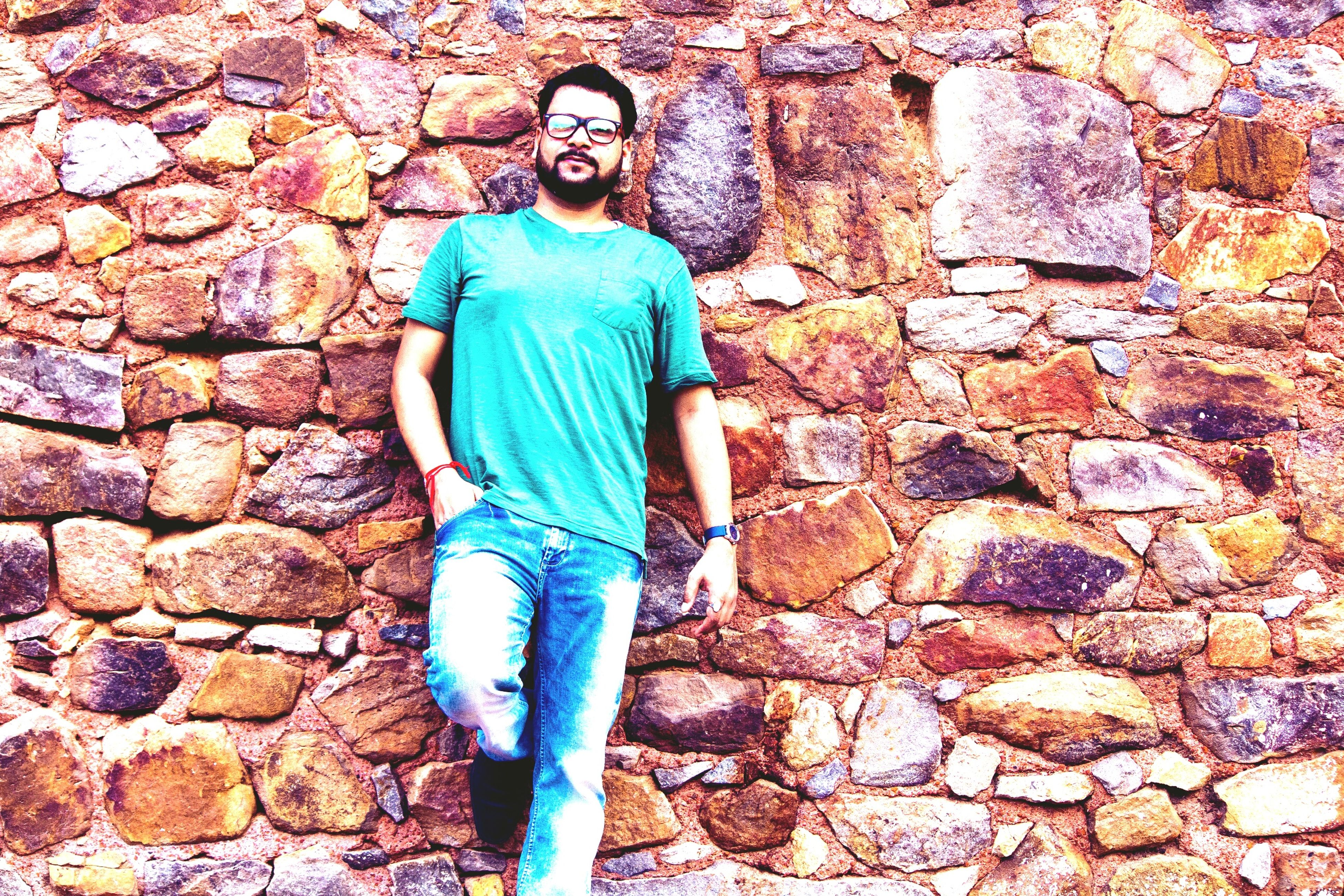 standing, stone wall, wall - building feature, lifestyles, three quarter length, person, blue, casual clothing, young adult, day, footpath, attitude