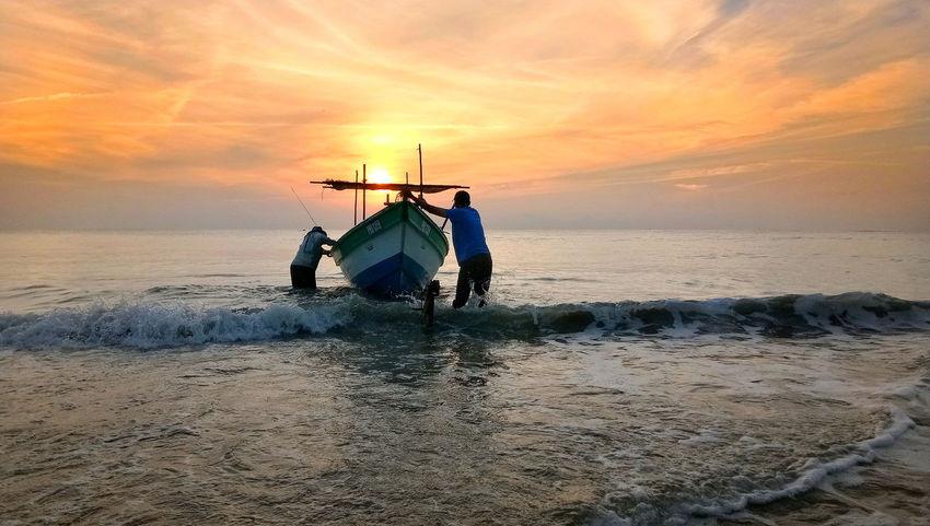 Sea Sun Sky Horizon Over Water Beach Landscape Orange Sky Boats And Sea Two Person. Fishermen's Life Waves Breaking