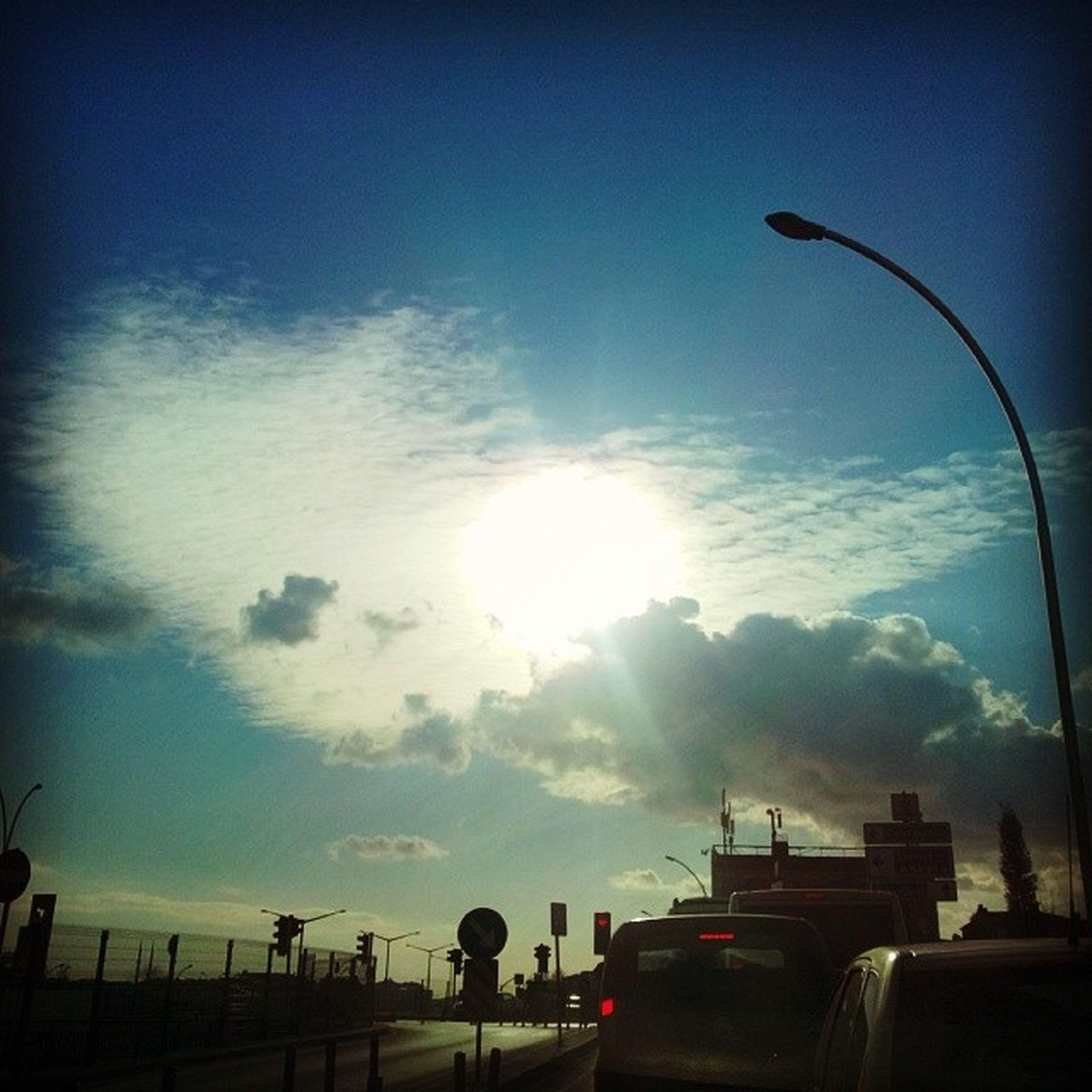 sky, transportation, sun, car, silhouette, cloud - sky, mode of transport, land vehicle, sunset, sunbeam, sunlight, lens flare, street light, low angle view, road, cloud, nature, street, outdoors, beauty in nature