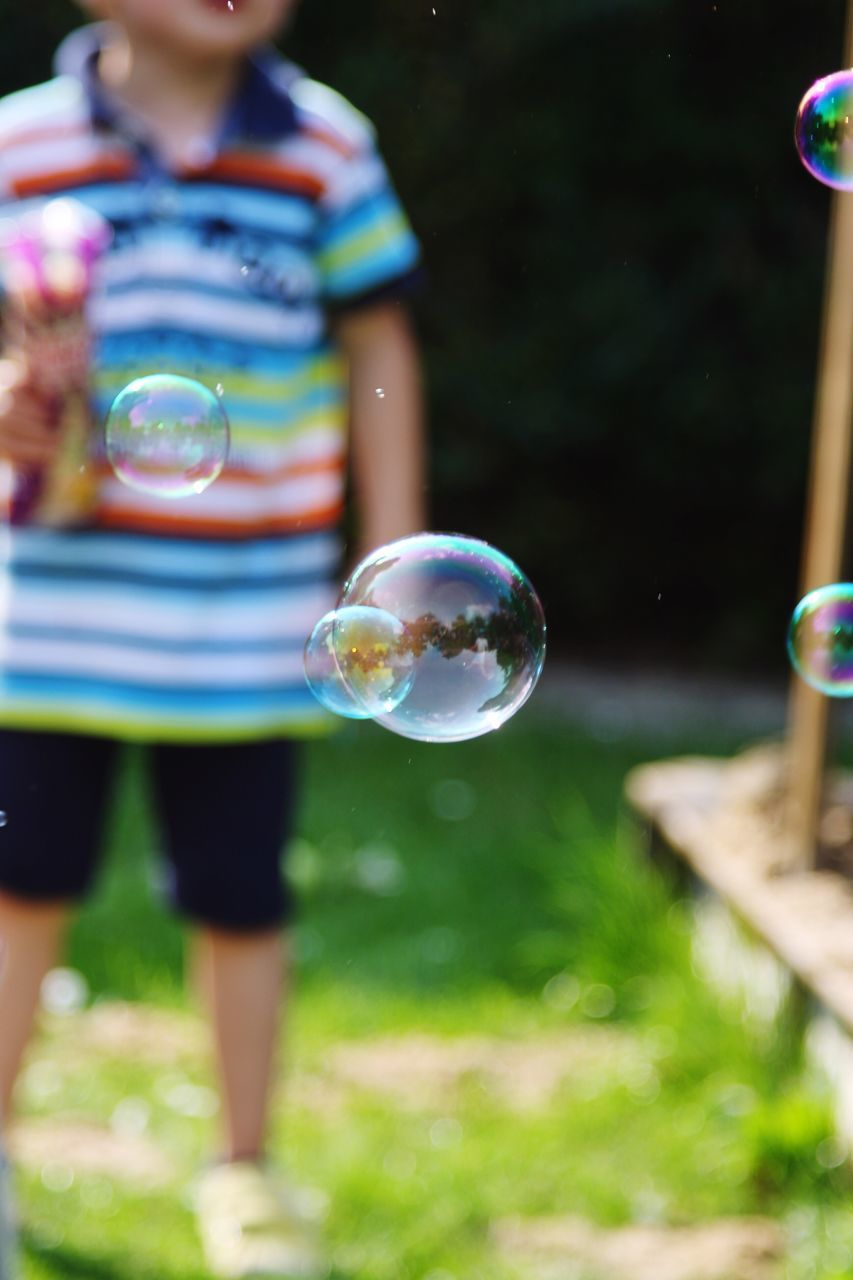 Bubbles In Mid-Air With Boy Standing In Background At Lawn