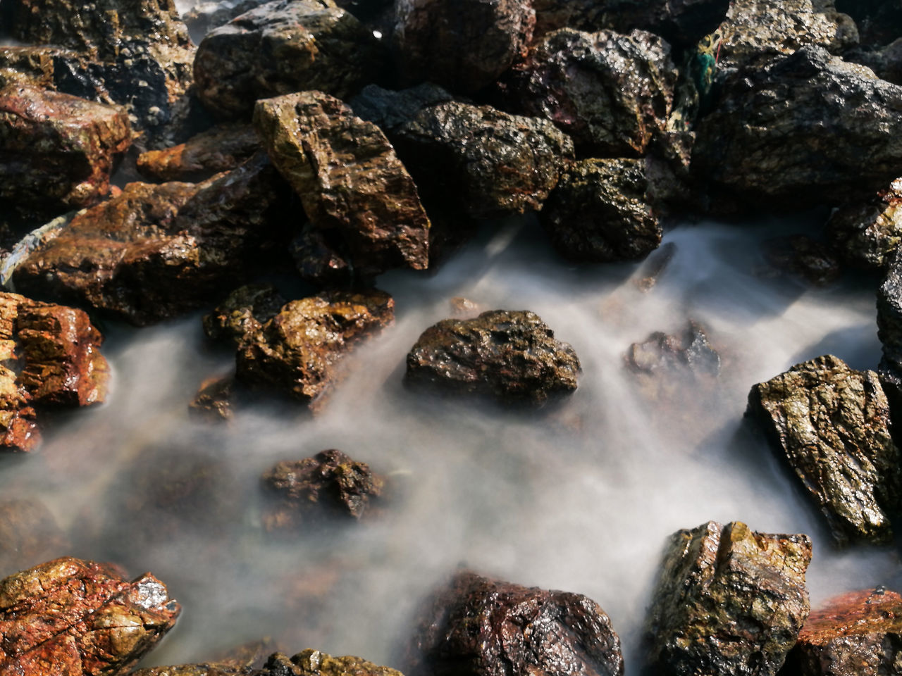 High Angle View Of Stream By Rocks