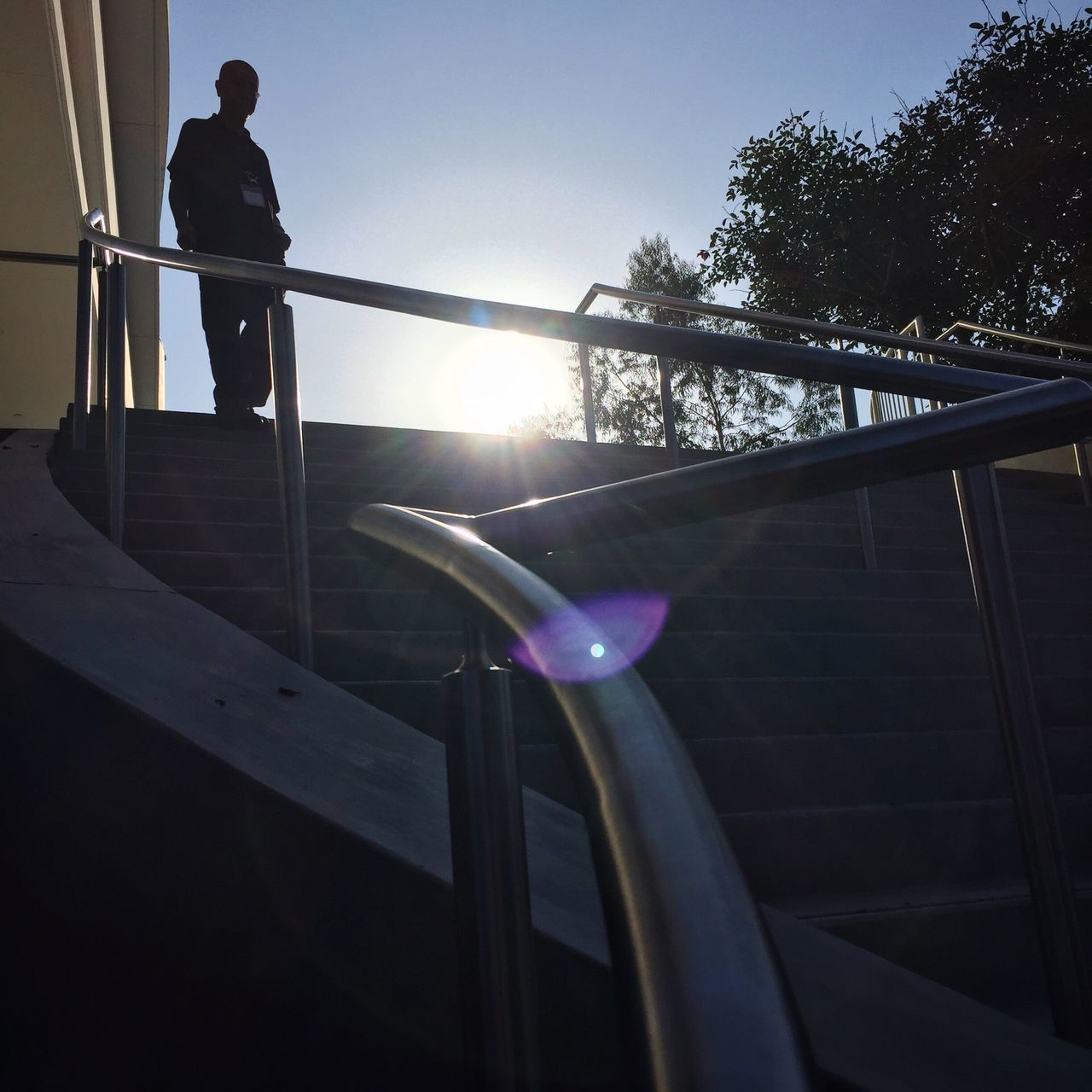 Waiting Game Silhouette of a man on top of a staircase. Real People Low Angle View One Person Sunbeam Sun Men Day Outdoors Silhouette Standing Lens Flare Sunny Trees Blue Sky People Stairs Building Railing Flare Sunlight Adult