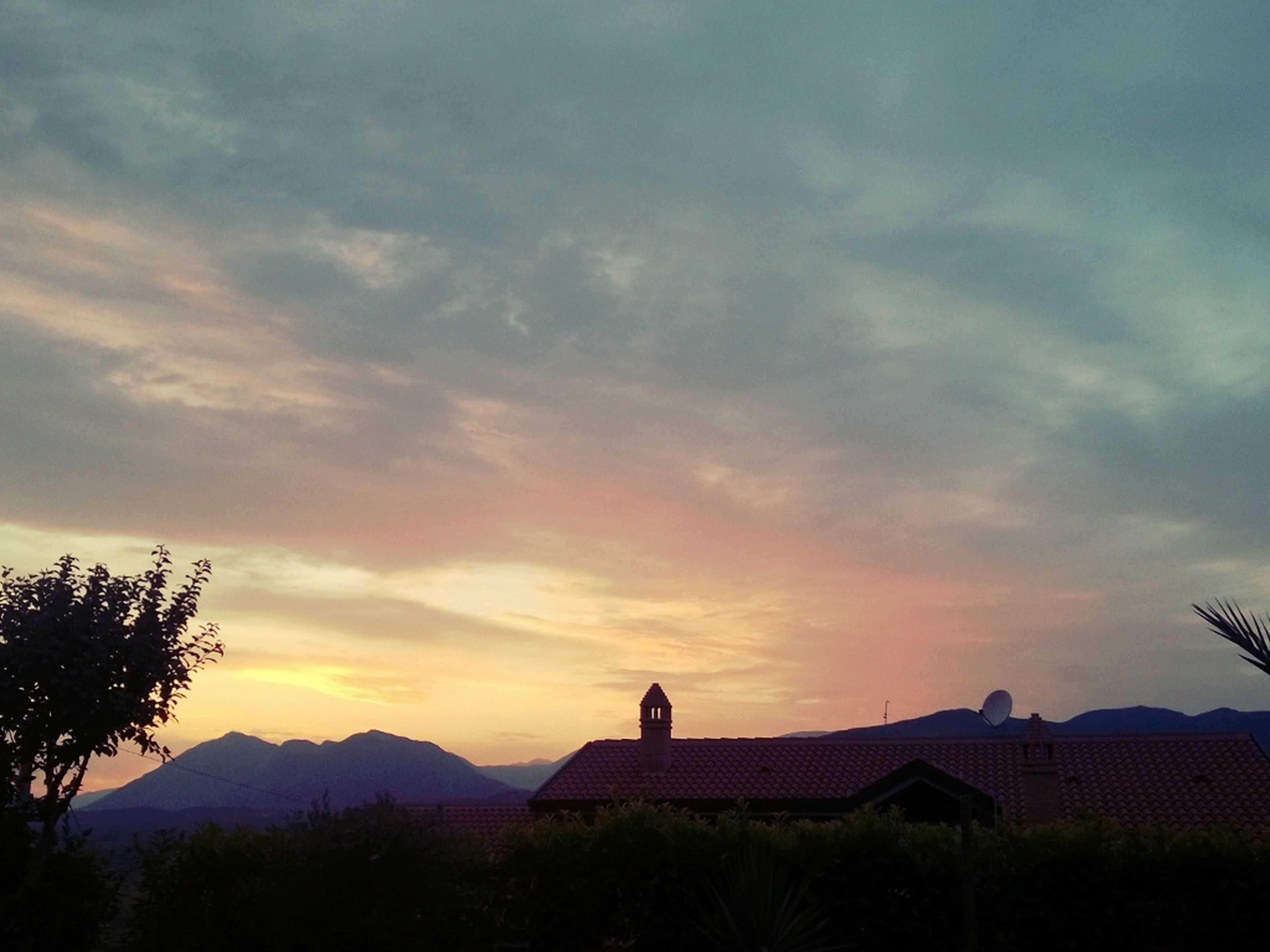 sunset, silhouette, sky, built structure, architecture, cloud - sky, building exterior, tree, beauty in nature, scenics, orange color, nature, cloudy, cloud, tranquility, tranquil scene, house, mountain, low angle view, idyllic