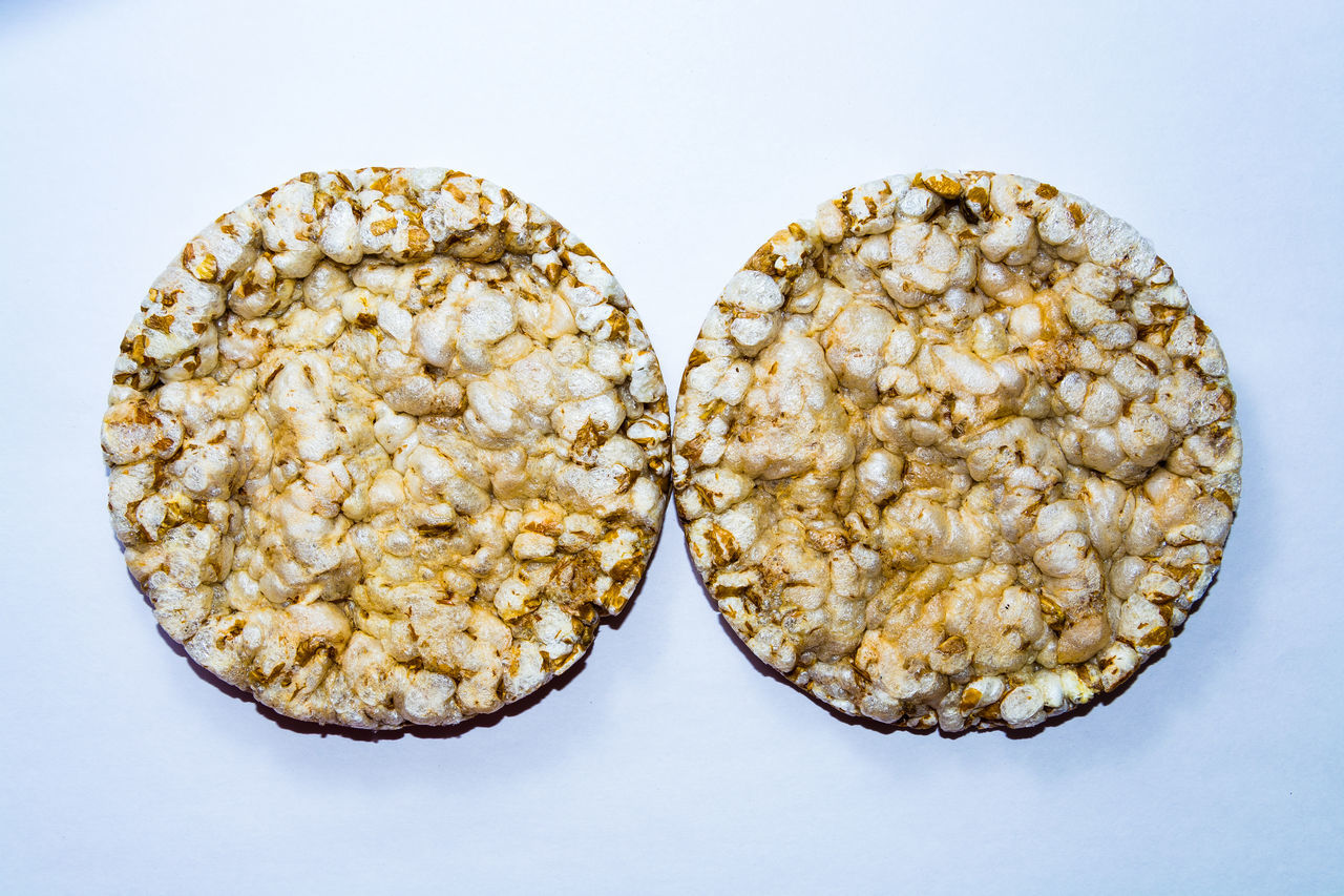 round whole grain crispbread closeup on a white background Baked Bread Brown Corn Crispbread  Crispy Food Freshness Grain Healthy Eating Heap Organic Snack Stack The OO Mission Wheat White Background Wholegrain