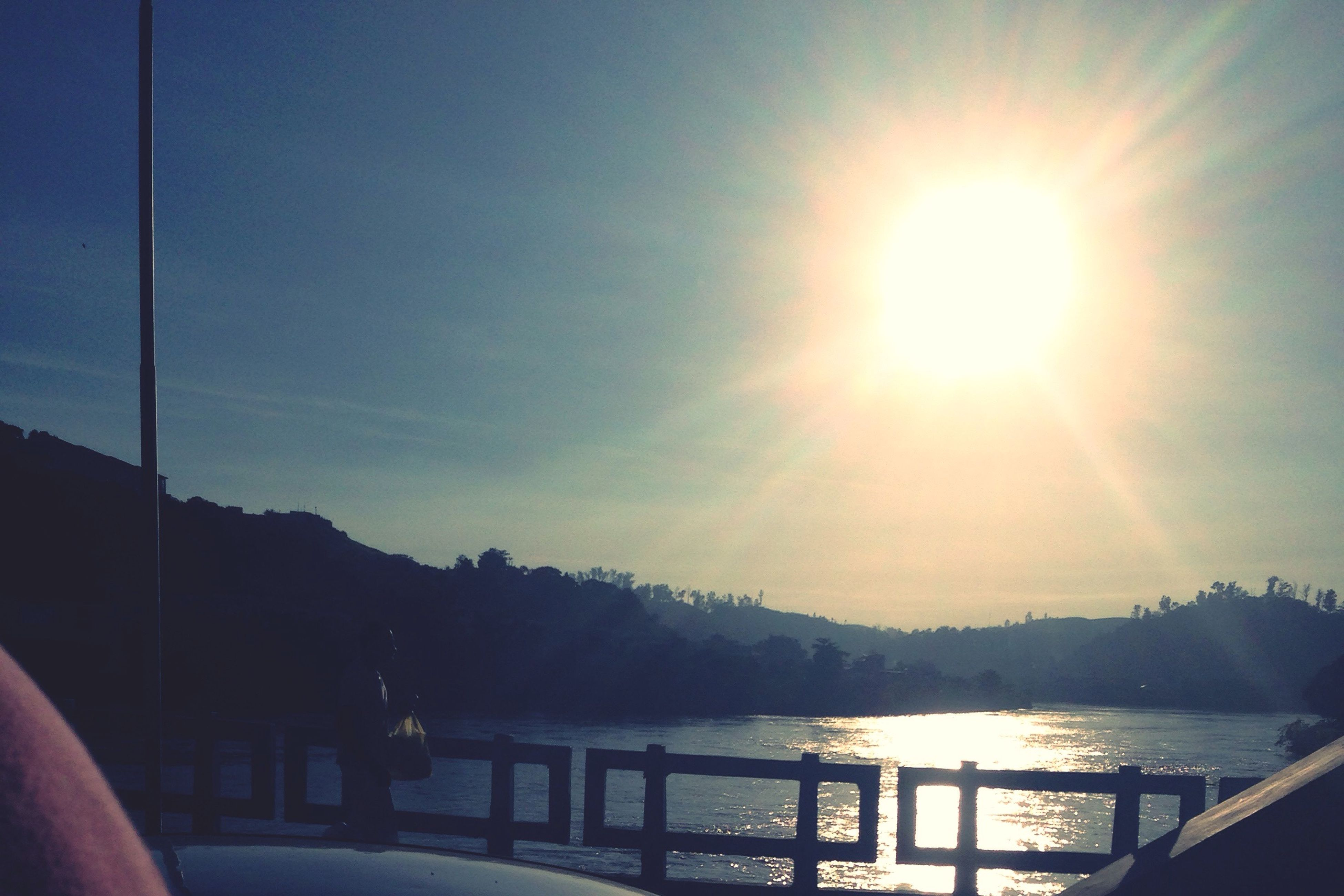 sun, sunbeam, water, sunlight, railing, lens flare, sky, beauty in nature, scenics, reflection, nature, tranquility, mountain, sunny, tranquil scene, silhouette, lake, river, sea