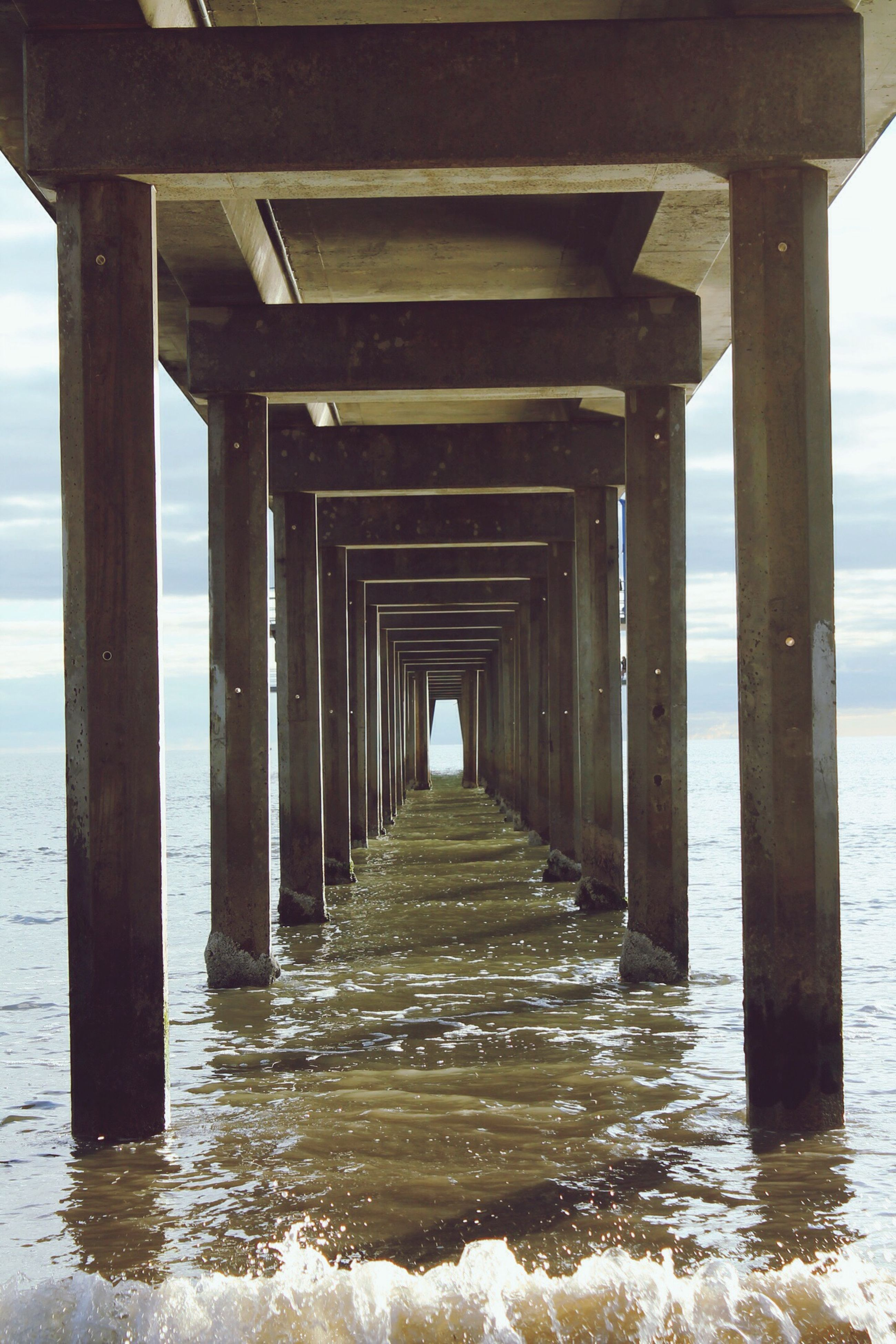 built structure, water, pier, architecture, support, architectural column, connection, in a row, low angle view, below, sea, column, beach, bridge - man made structure, wave, long, underneath, engineering, diminishing perspective, shore, day, supported, nature, bridge, the way forward, tranquil scene, no people, vanishing point, tranquility, scenics