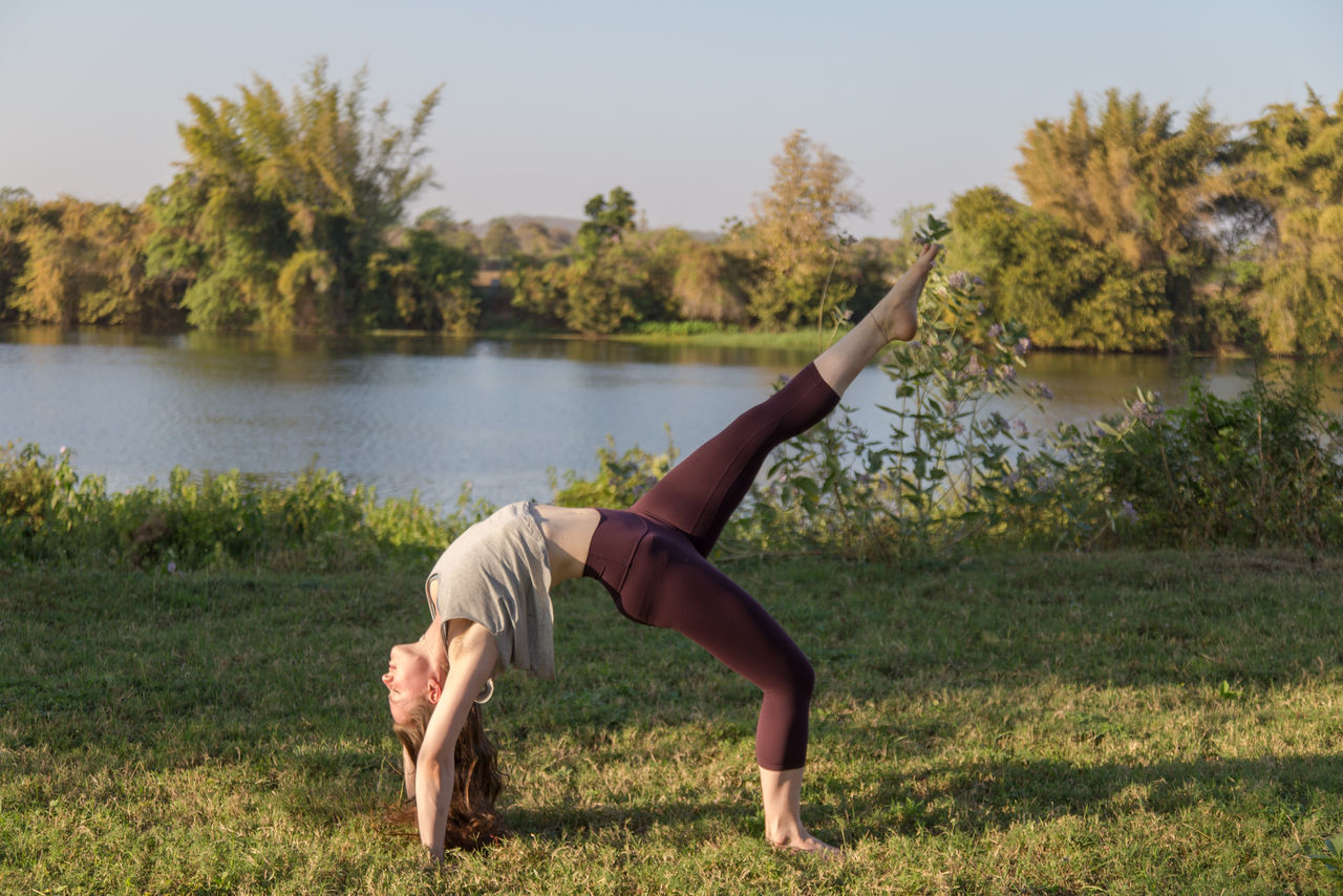 yoga, balance, water, exercising, tree, real people, lake, full length, outdoors, lifestyles, day, nature, leisure activity, one person, grass, flexibility, beauty in nature, healthy lifestyle, young women, sports clothing, young adult, sky, mammal