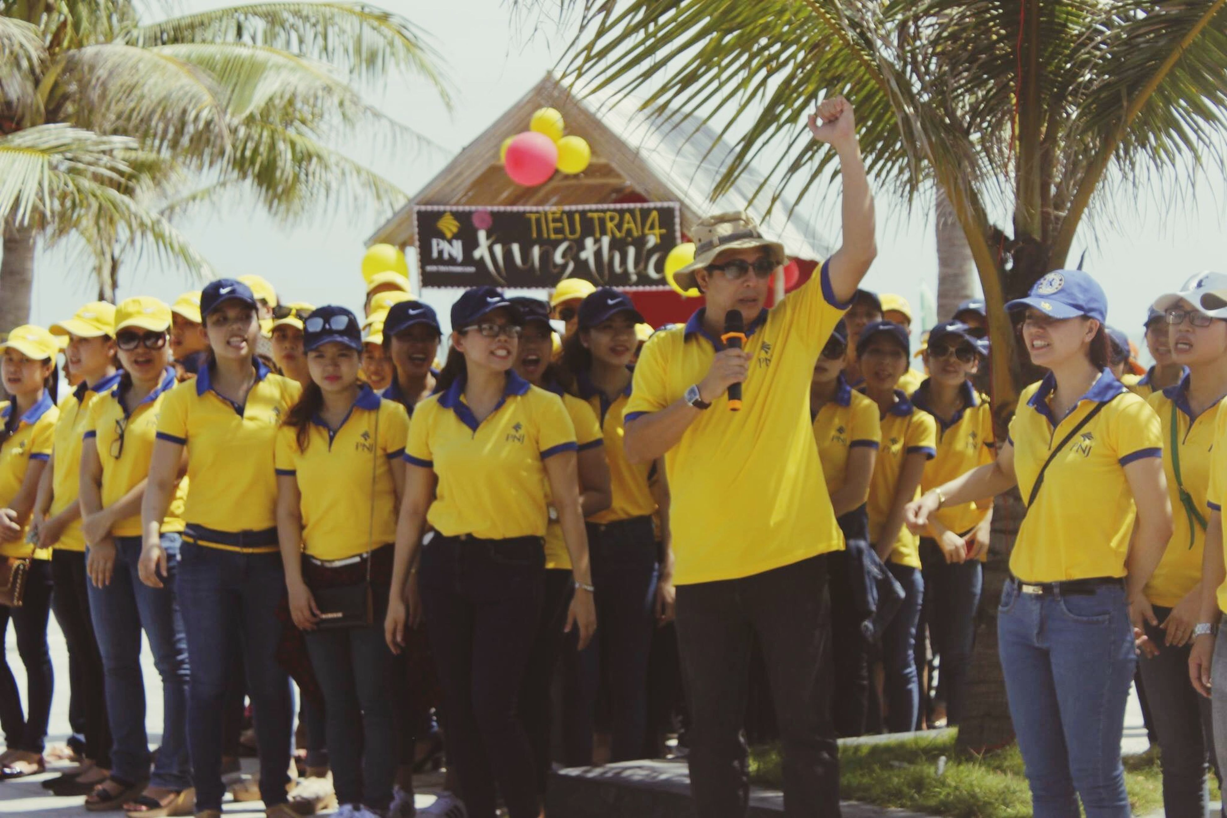men, large group of people, person, lifestyles, leisure activity, walking, text, standing, crowd, rear view, street, casual clothing, day, outdoors, togetherness, yellow, mixed age range, celebration, western script