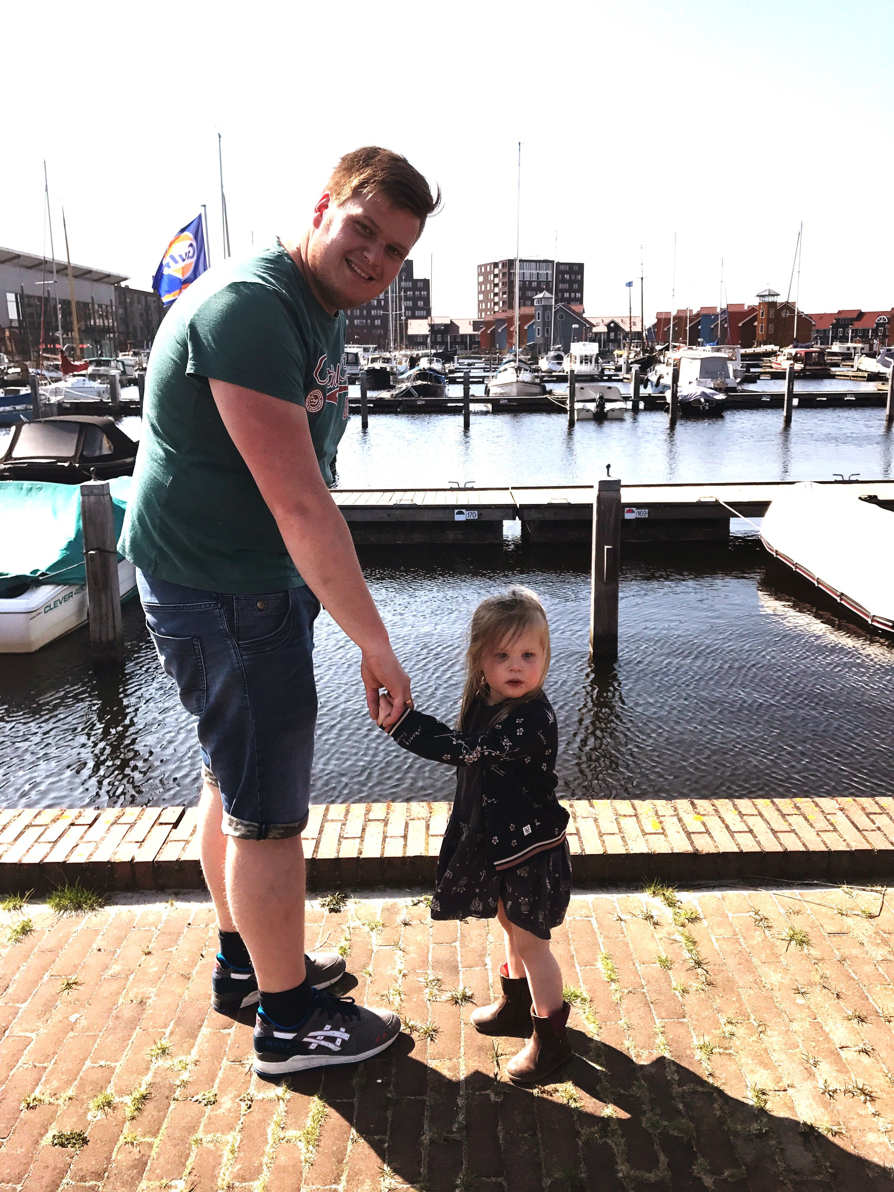 real people, full length, casual clothing, river, two people, standing, togetherness, water, day, harbor, love, leisure activity, outdoors, nautical vessel, childhood, lifestyles, built structure, young women, moored, young adult, happiness, building exterior, architecture, sky
