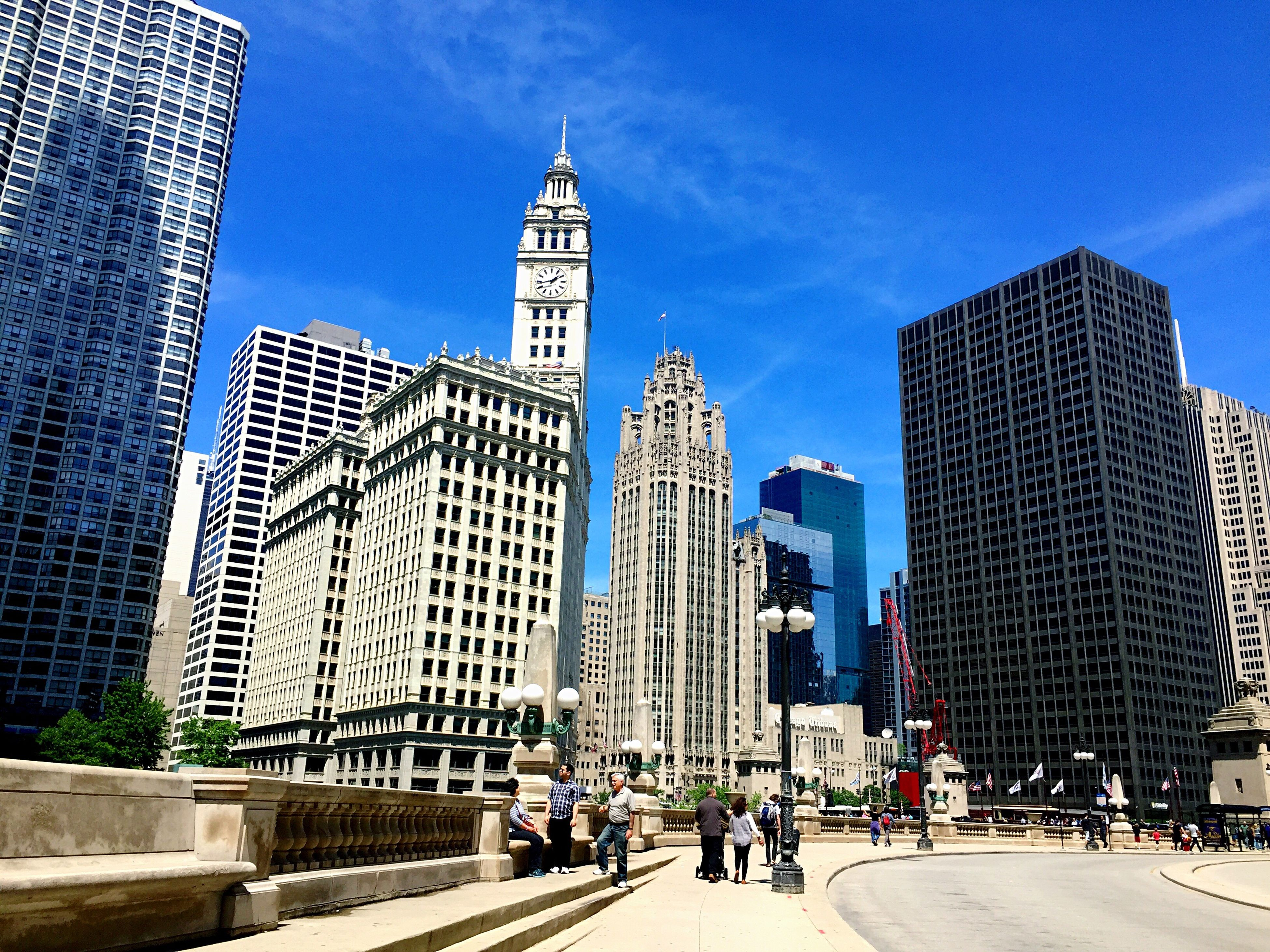 architecture, skyscraper, building exterior, built structure, city, tall - high, tower, modern, city life, travel destinations, sky, day, blue, outdoors, low angle view, large group of people, tall, downtown district, cityscape, real people, clear sky, urban skyline, office park, people