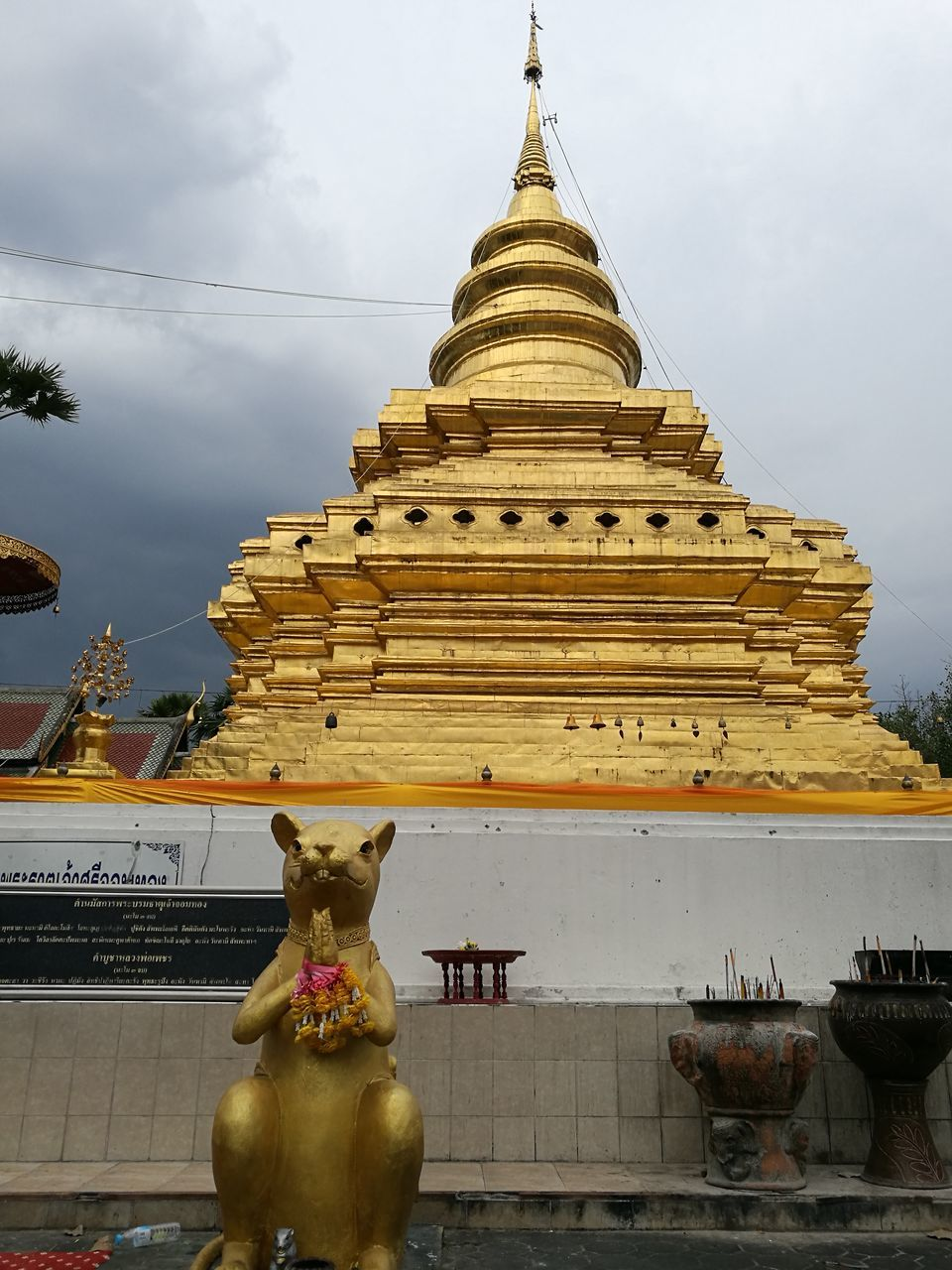 religion, spirituality, statue, architecture, place of worship, built structure, building exterior, sculpture, gold colored, pagoda, human representation, sky, history, ancient, travel destinations, outdoors, low angle view, no people, day, gold