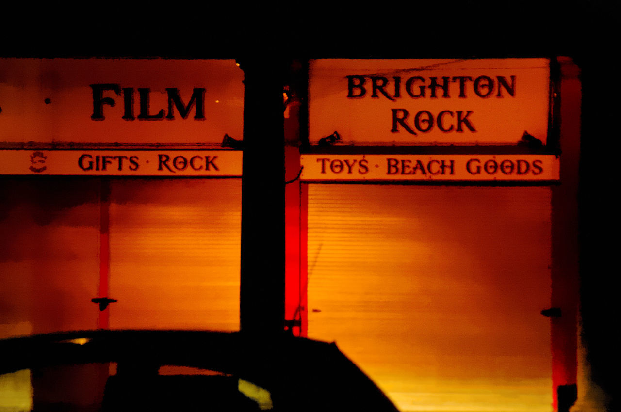 The street lights make this closed shop front look orange. A reference to the movie Brighton Rock appears on the shop sign Advertising Brighton Rock Closed Dark Night Orange Shadow Shadows Shop Shutters Learn & Shoot: After Dark Cities At Night