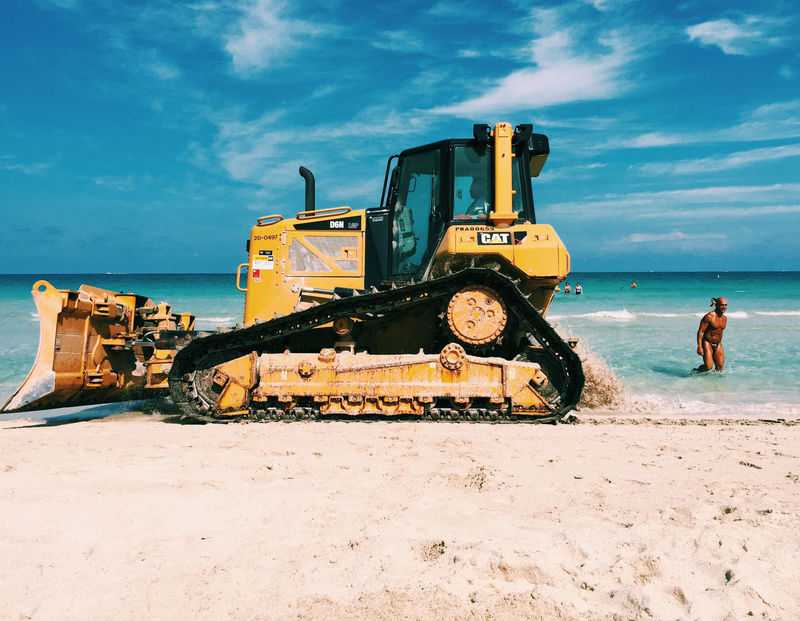 Beach Bold Commercial Land Vehicle Construction Equipment Construction Industry Construction Machinery Construction Site Construction Vehicle Day Digging Earth Mover Industrial Equipment Industry Land Vehicle Machinery No People Outdoors Road Construction Sea Sky Tractor