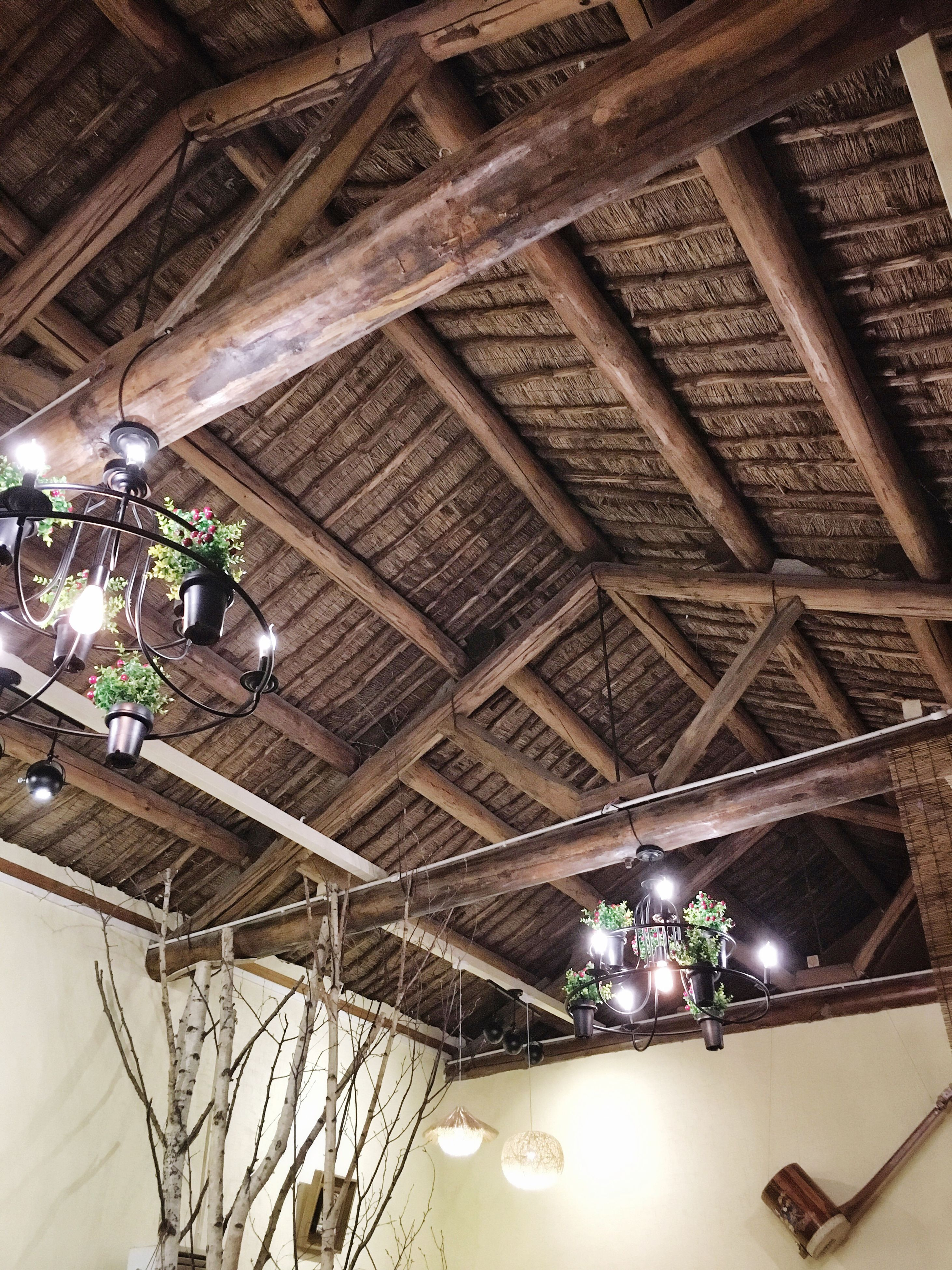 ceiling, indoors, low angle view, roof beam, architecture, illuminated, lighting equipment, built structure, ceiling fan, roof, modern, real people, day
