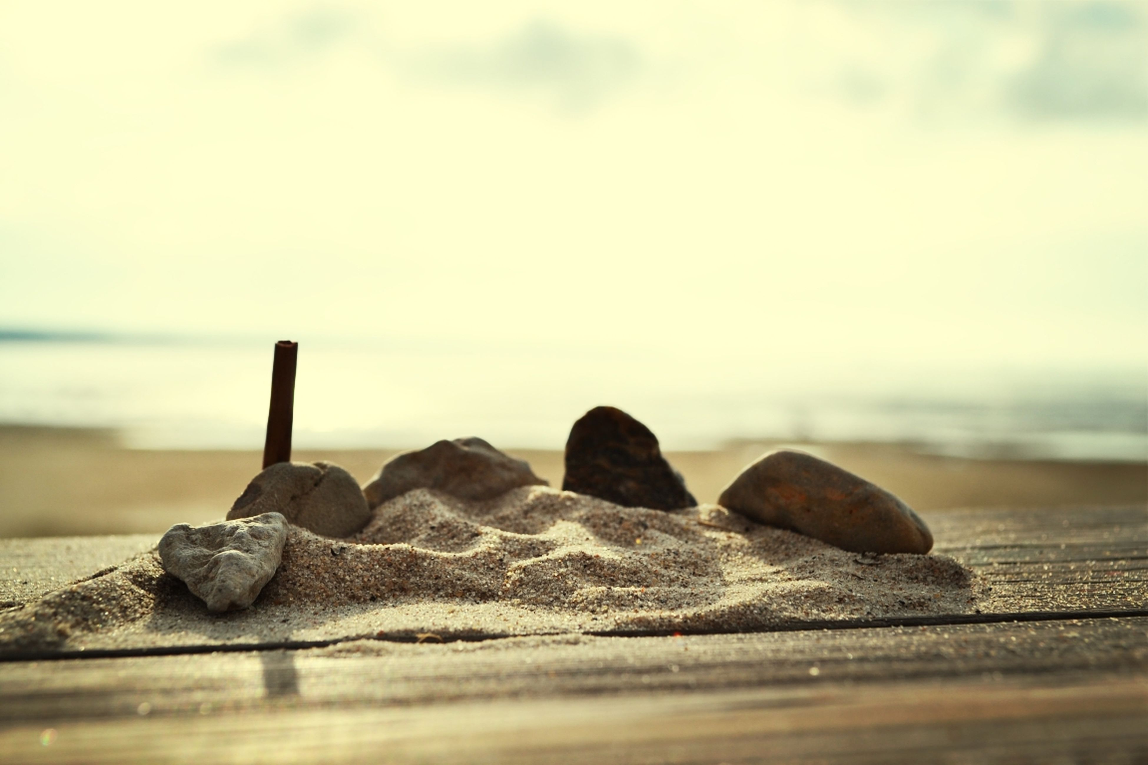 sky, sea, surface level, focus on foreground, selective focus, tranquility, beach, tranquil scene, water, nature, close-up, rock - object, pebble, wood - material, day, scenics, shore, outdoors, stone - object, beauty in nature