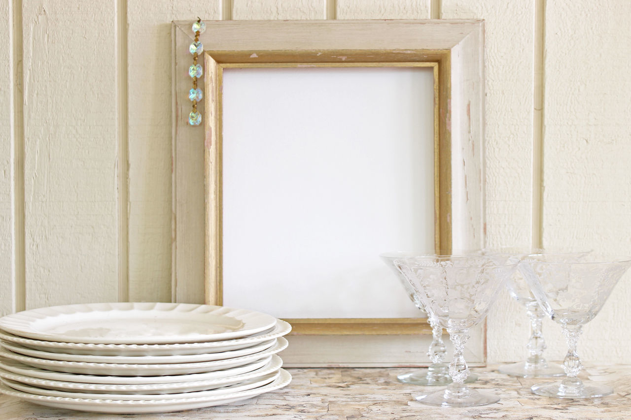 Picture Frame By Plates And Wineglasses On Table