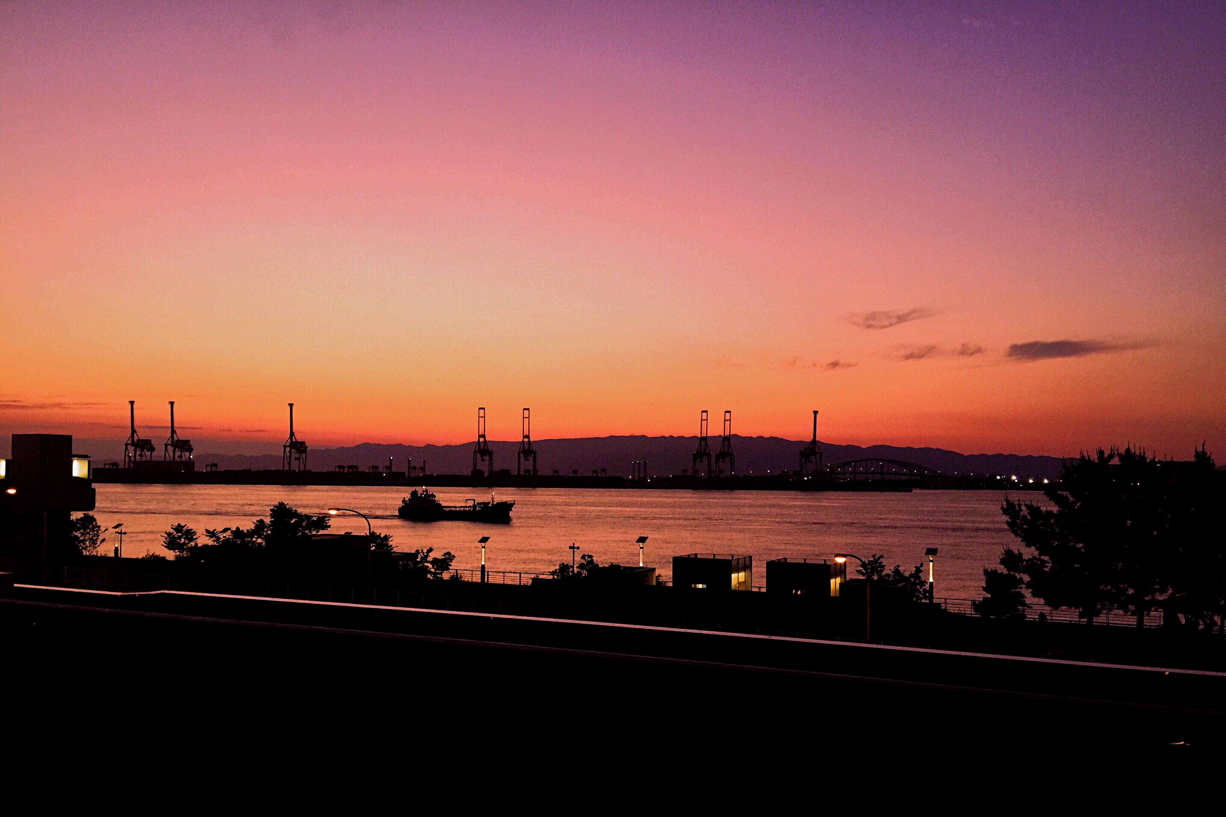sunset, silhouette, orange color, transportation, copy space, water, built structure, architecture, sky, river, mode of transport, clear sky, nautical vessel, dusk, scenics, building exterior, beauty in nature, nature, connection, bridge - man made structure