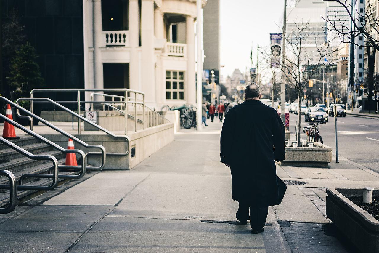 Rear View Of Man In Winter Coat Walking On Sidewalk