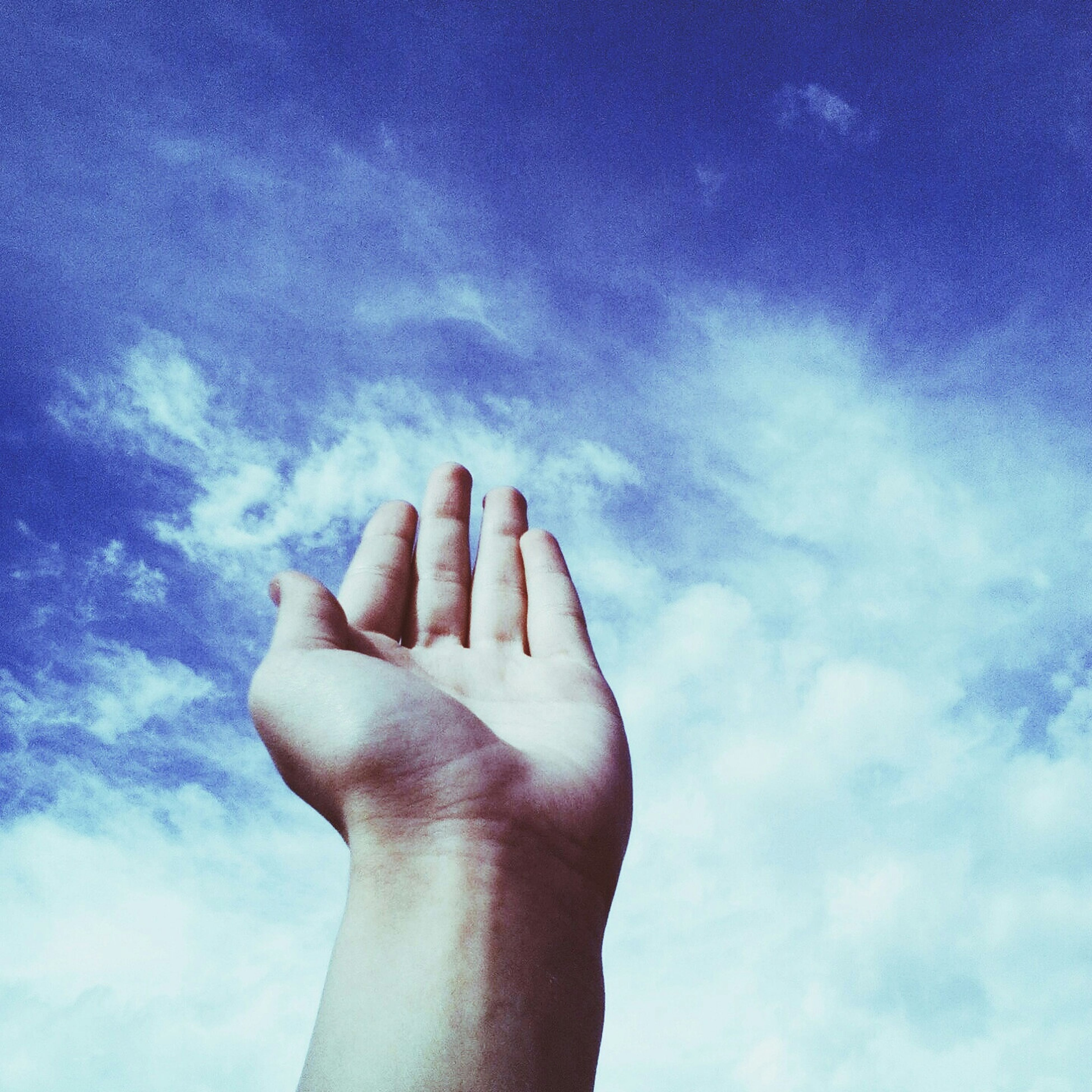 person, part of, personal perspective, sky, human finger, cropped, low angle view, holding, cloud - sky, blue, unrecognizable person, cloud, close-up, day, outdoors, showing, cloudy