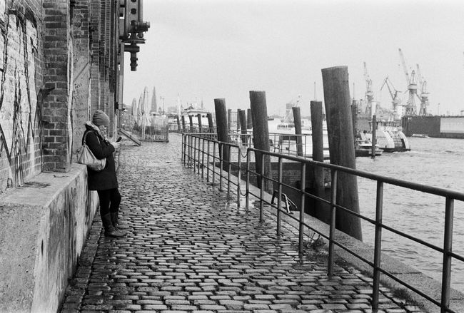 Zwei Zeiten, Contessa, Ilford HP5 400 35mm Adult Adults Only Architecture Believeinfilm Building Exterior Built Structure City Cityscape Cobblestone Day Elbe Filmisnotdead Hamburg Harbour Harbor Harbour One Person Outdoors People Real People Sky Smartphone Travel Destinations Urban Water