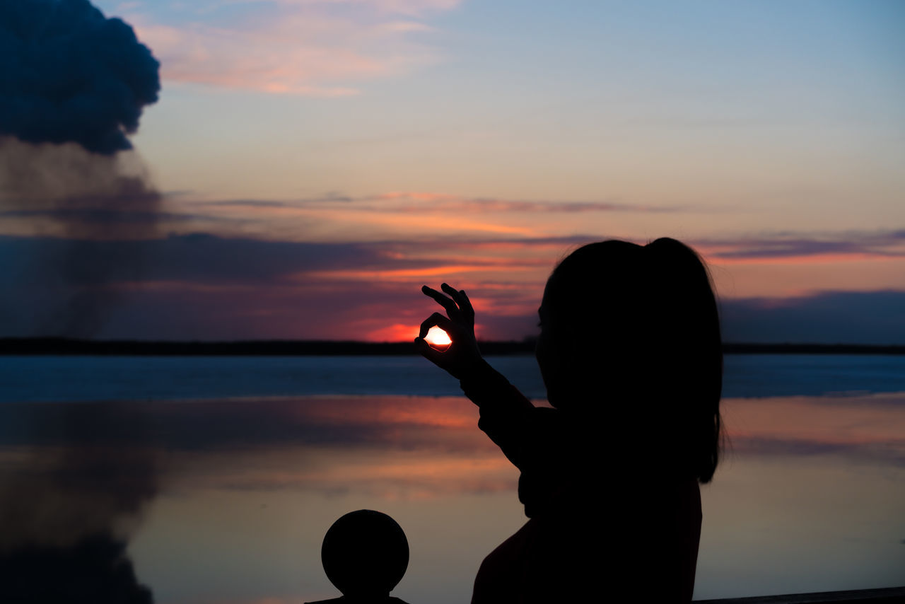 Beauty In Nature Cloud Cloud - Sky Cloudy Focus On Foreground Holding Idyllic Leisure Activity Lifestyles Nature Orange Color Outdoors Part Of Scenics Sky Sunset Tranquil Scene Tranquility Unrecognizable Person