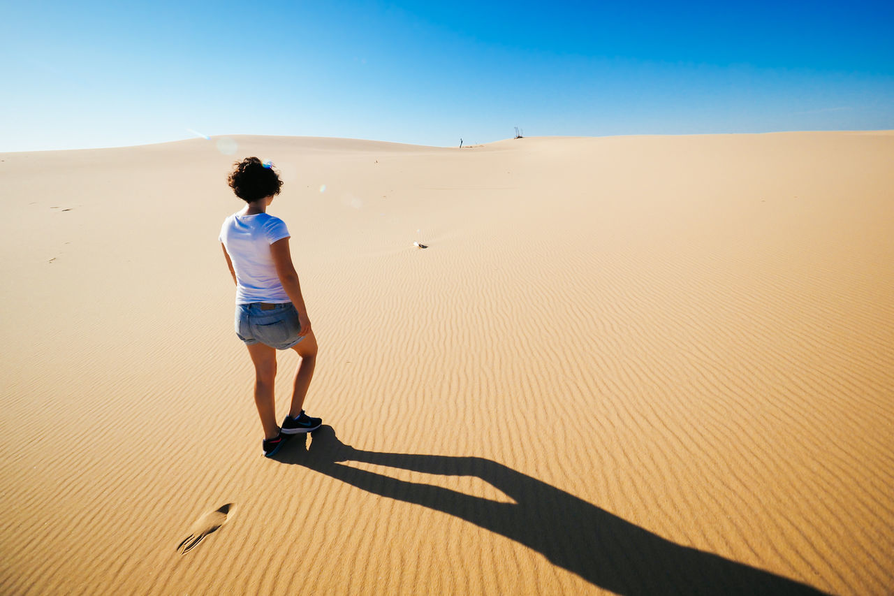 Arid Climate Beach Clear Sky Day Desert Desert Epic Full Length Heat - Temperature Isolated Lifestyles Lonely Nature One Person Outdoors People Real People Rear View Sand Sand Dune Shorts Vast