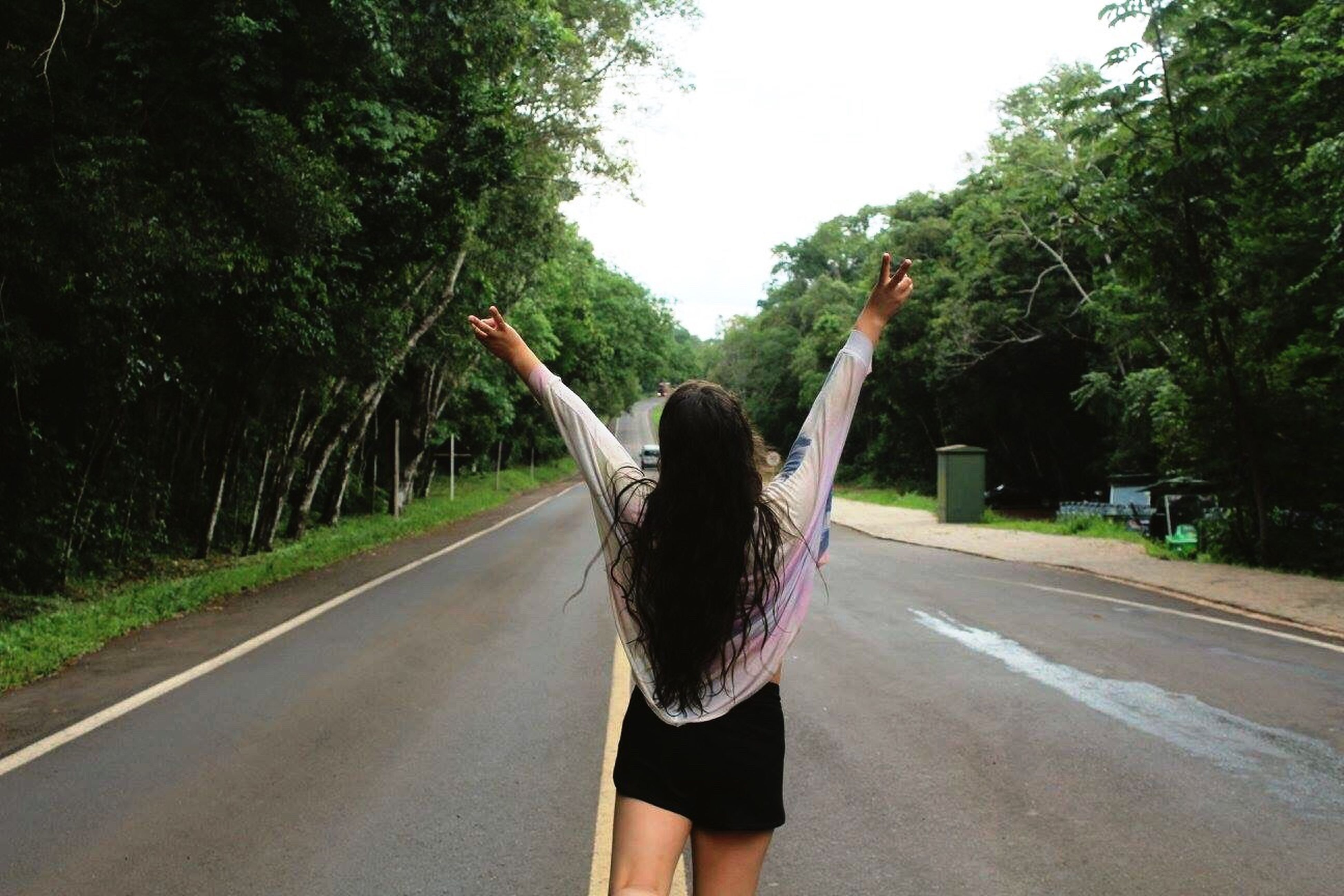 rear view, road, only women, tree, one woman only, adults only, human body part, one person, people, the way forward, hand raised, outdoors, adult, young adult, day, one young woman only, nature, human hand, sky