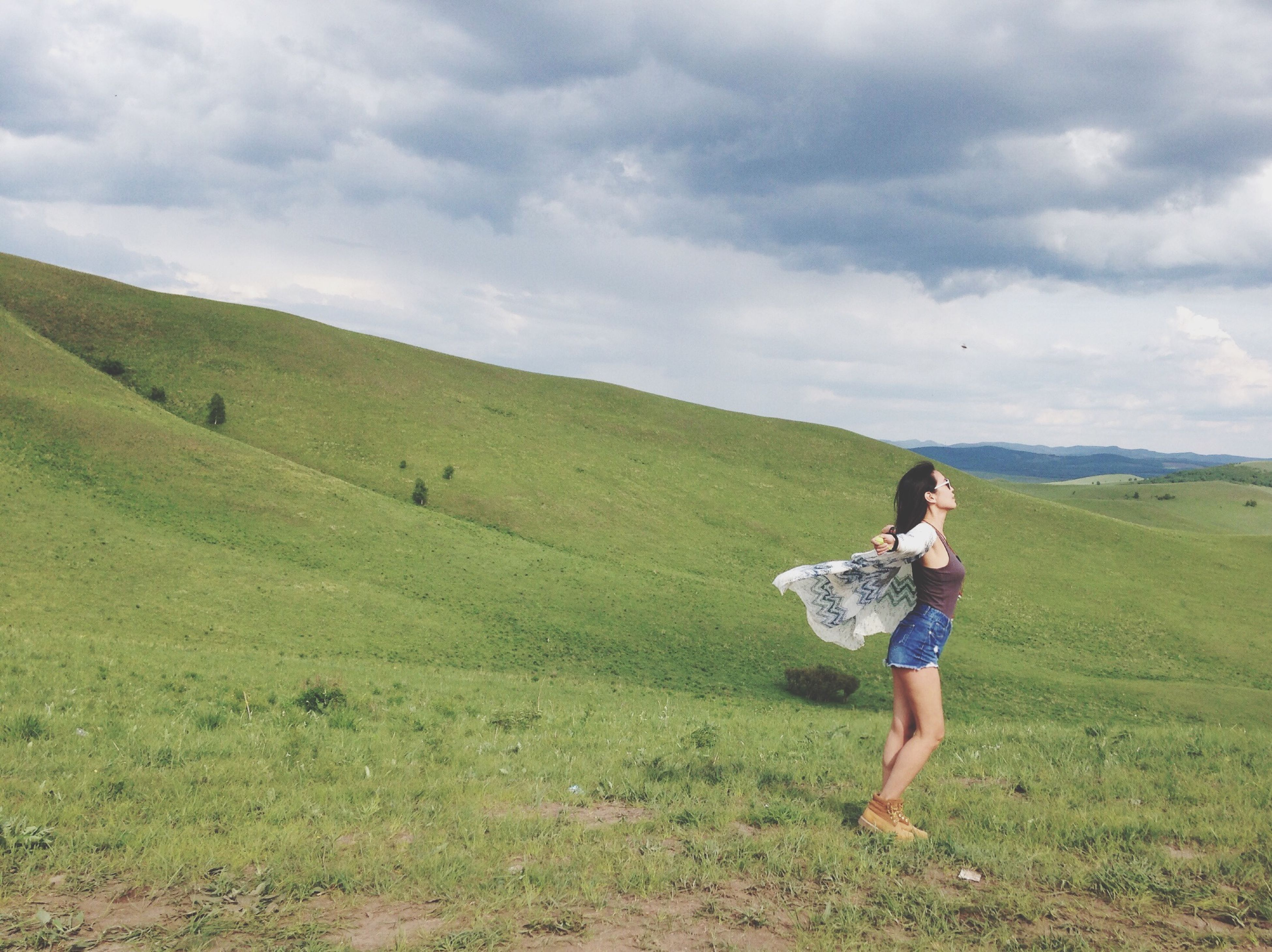 full length, sky, grass, lifestyles, casual clothing, leisure activity, landscape, field, cloud - sky, rear view, person, tranquil scene, nature, cloudy, young adult, tranquility, beauty in nature, standing
