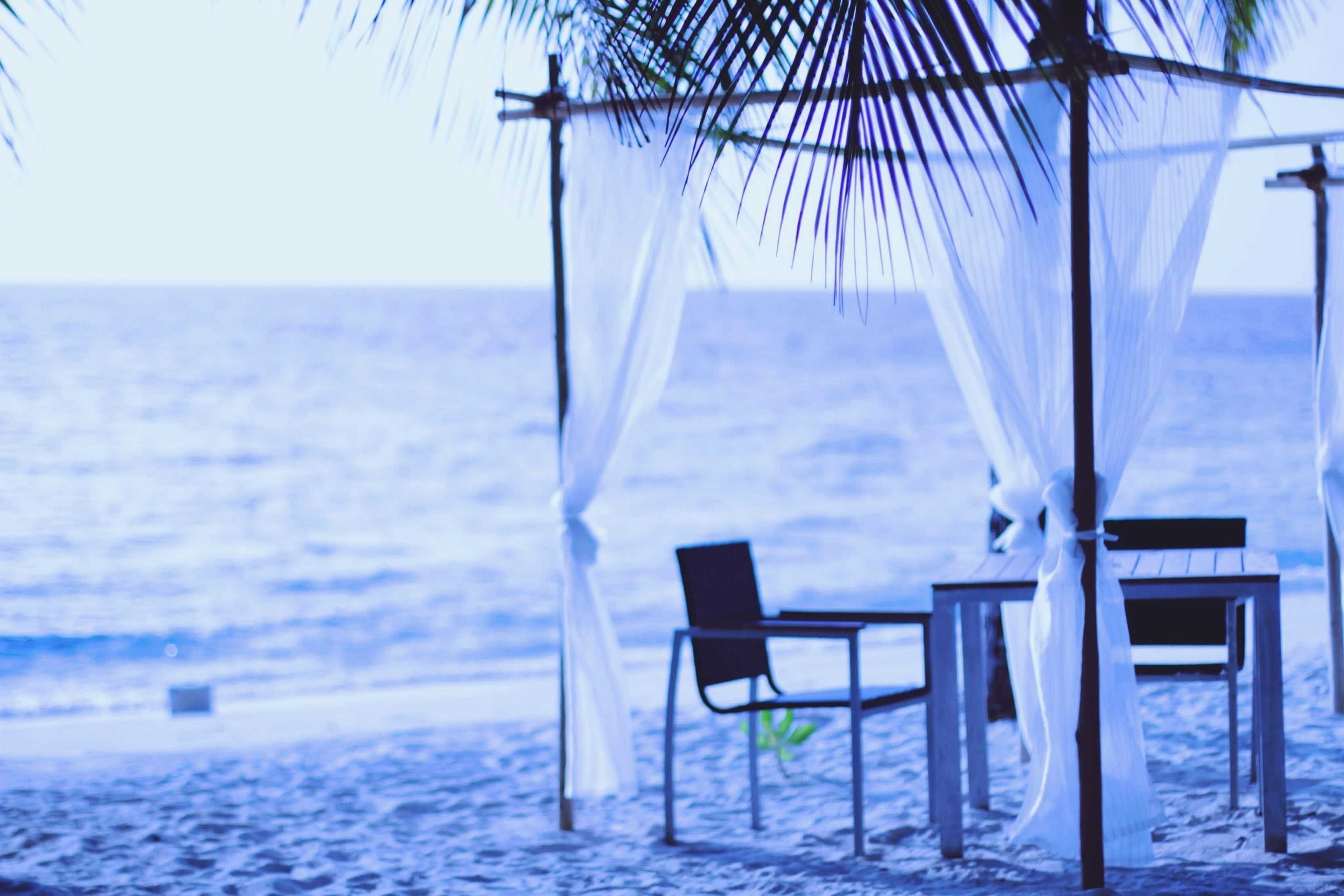 sea, chair, absence, empty, horizon over water, water, beach, table, tranquility, tranquil scene, seat, bench, sand, scenics, relaxation, sunlight, nature, beach umbrella, vacations, shore