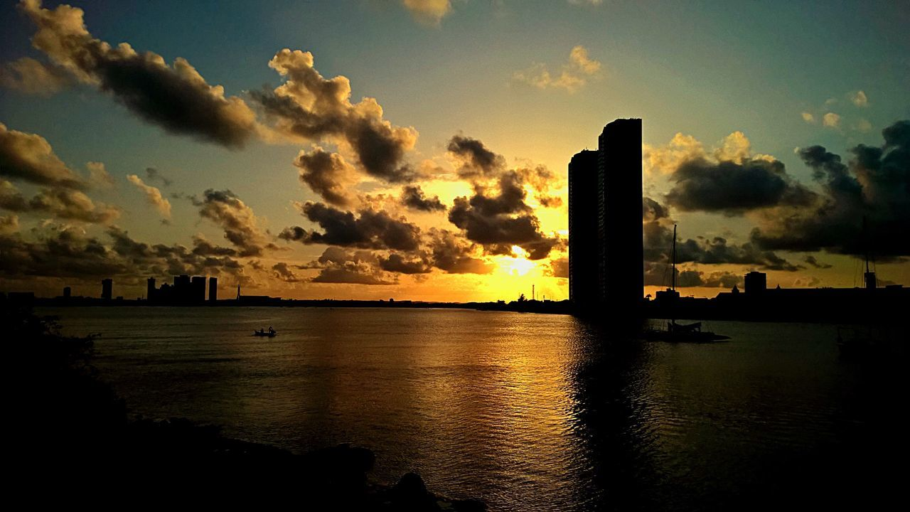 Sea By Silhouette Buildings In City During Sunset