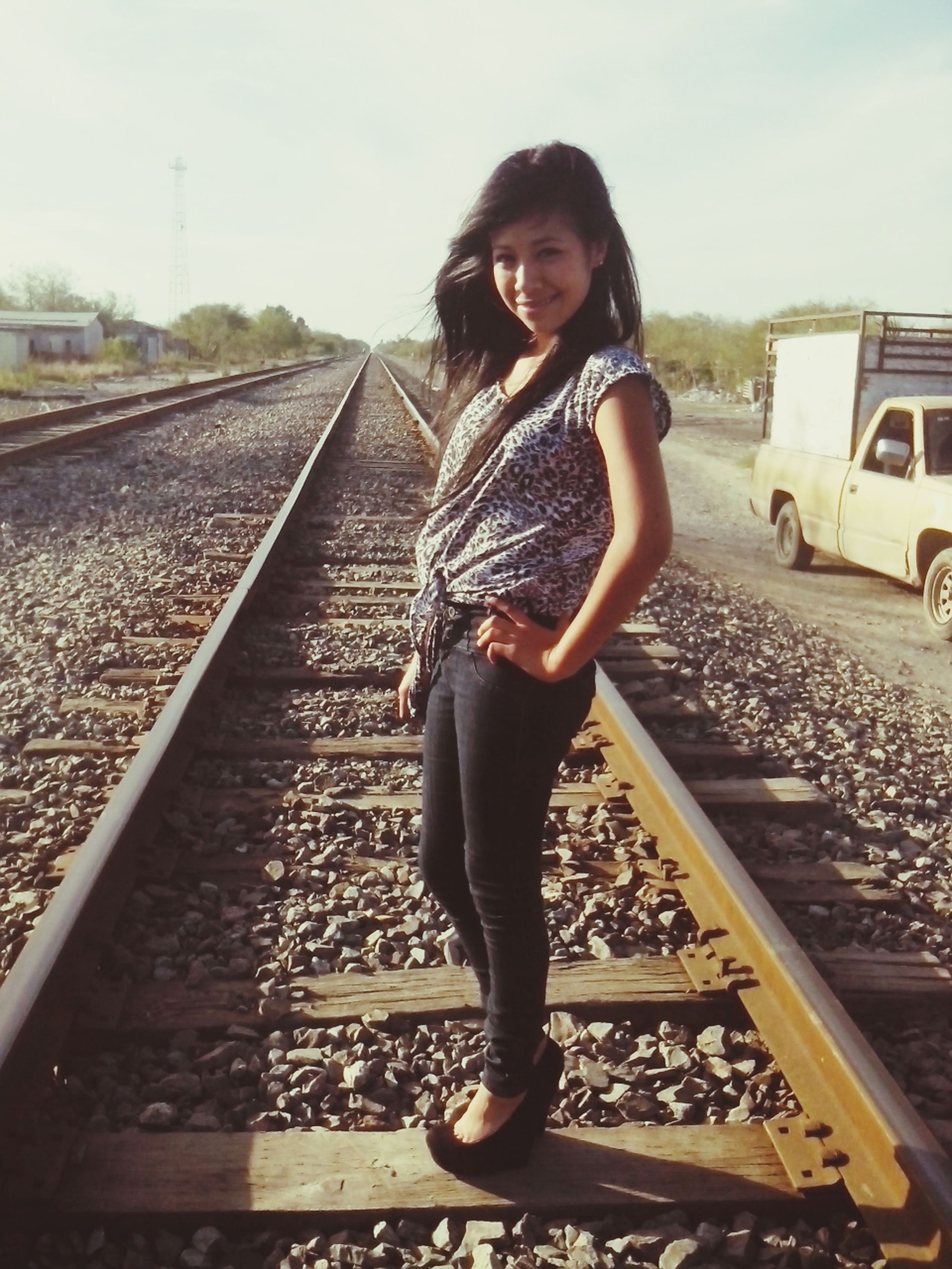 railroad track, young adult, lifestyles, transportation, casual clothing, person, portrait, looking at camera, rail transportation, young women, standing, full length, front view, leisure activity, public transportation, travel, smiling