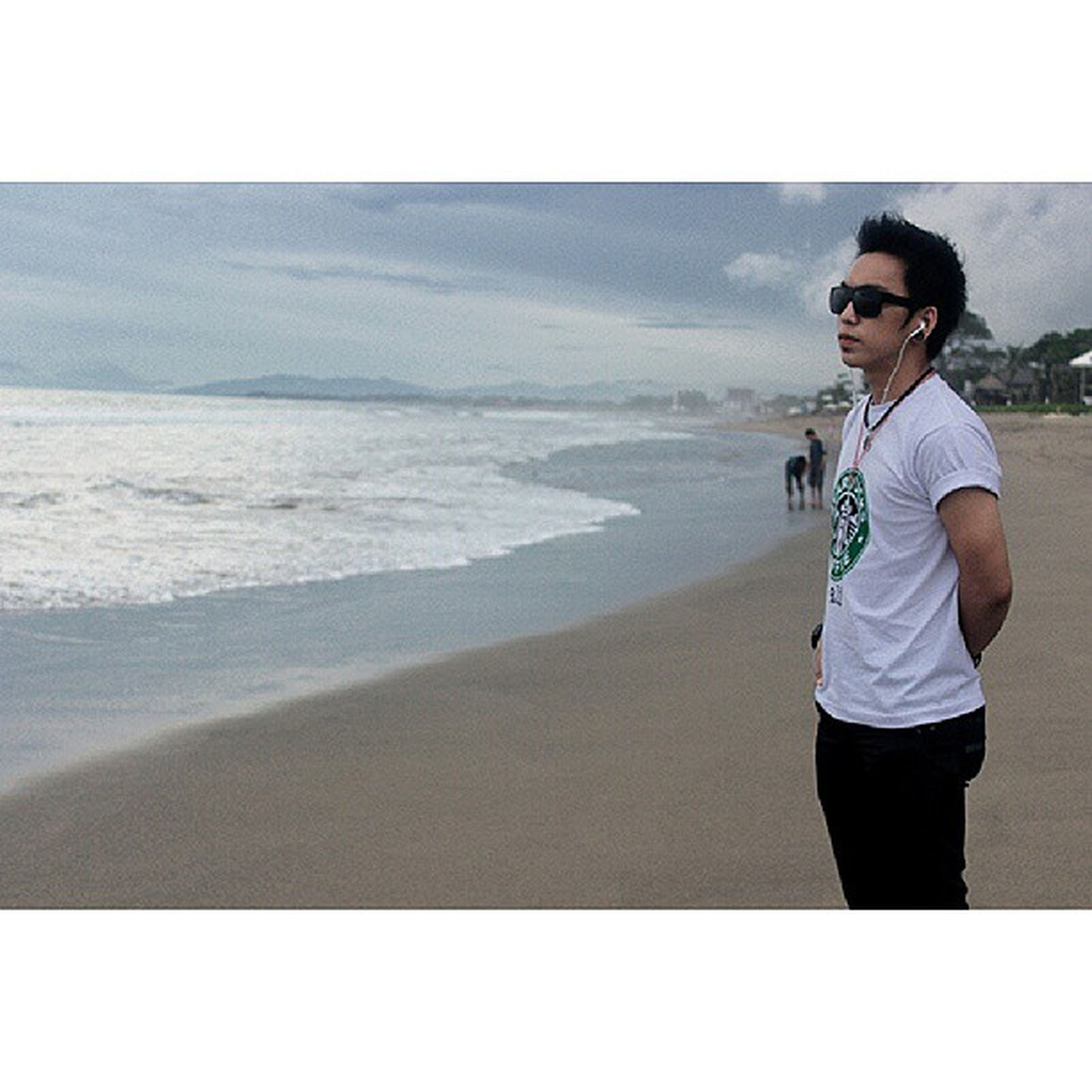 beach, lifestyles, leisure activity, sea, transfer print, full length, casual clothing, standing, water, shore, sand, auto post production filter, person, young adult, vacations, sky, horizon over water, young men