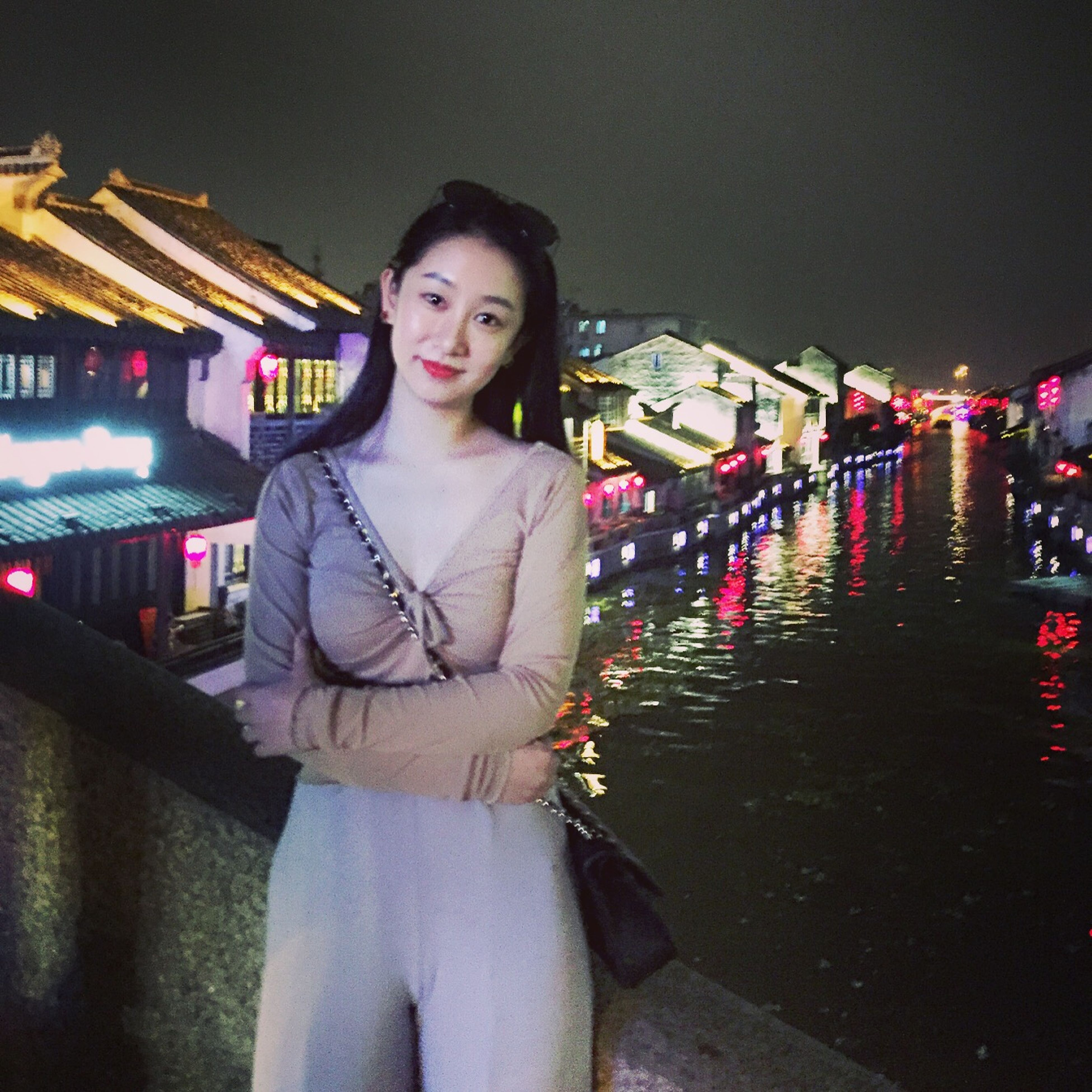 lifestyles, night, standing, young adult, looking at camera, person, casual clothing, front view, portrait, three quarter length, leisure activity, young women, built structure, illuminated, waist up, smiling, building exterior, architecture