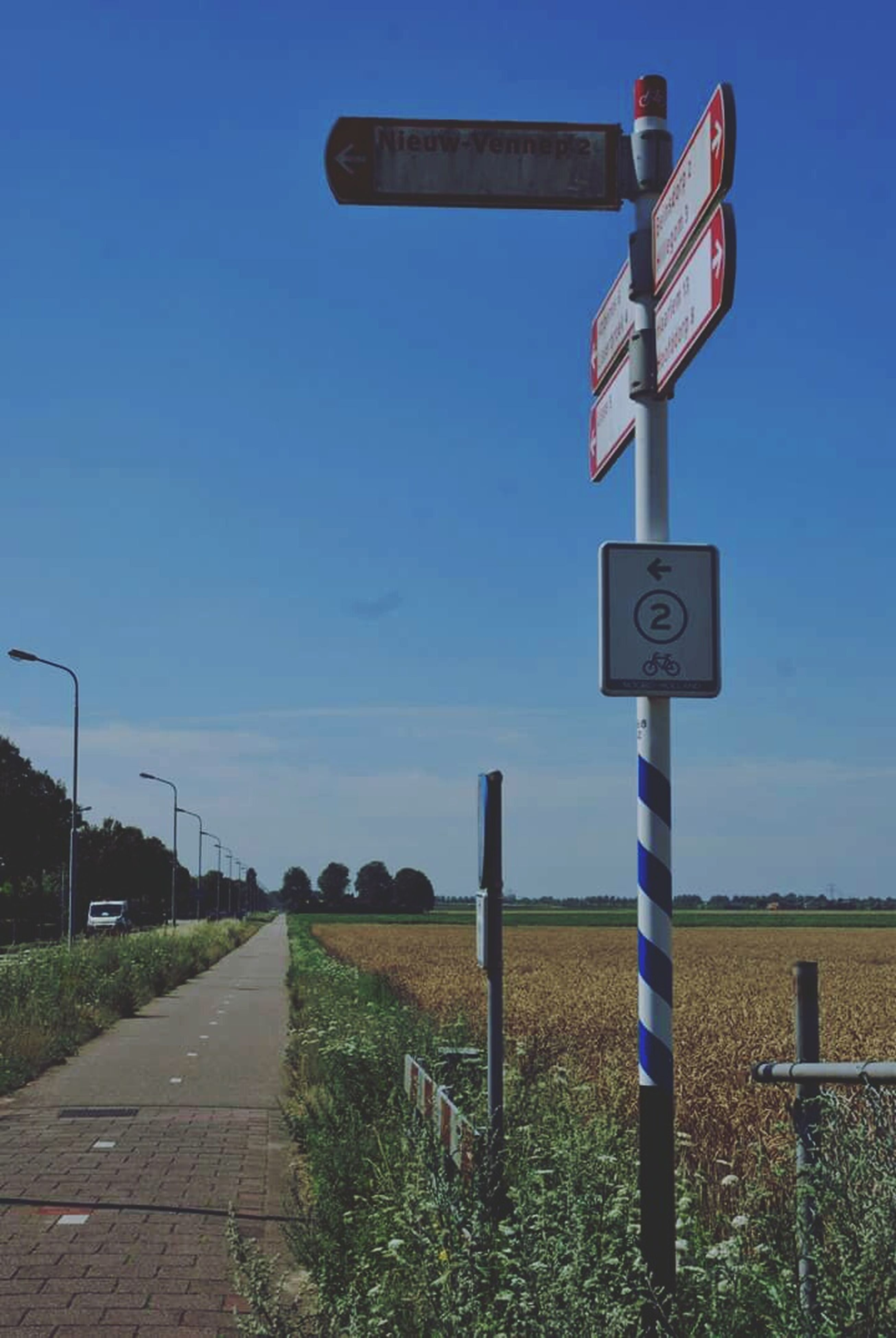 guidance, road sign, communication, blue, clear sky, sign, direction, information sign, arrow symbol, grass, text, western script, field, directional sign, sky, copy space, landscape, pole, road, the way forward