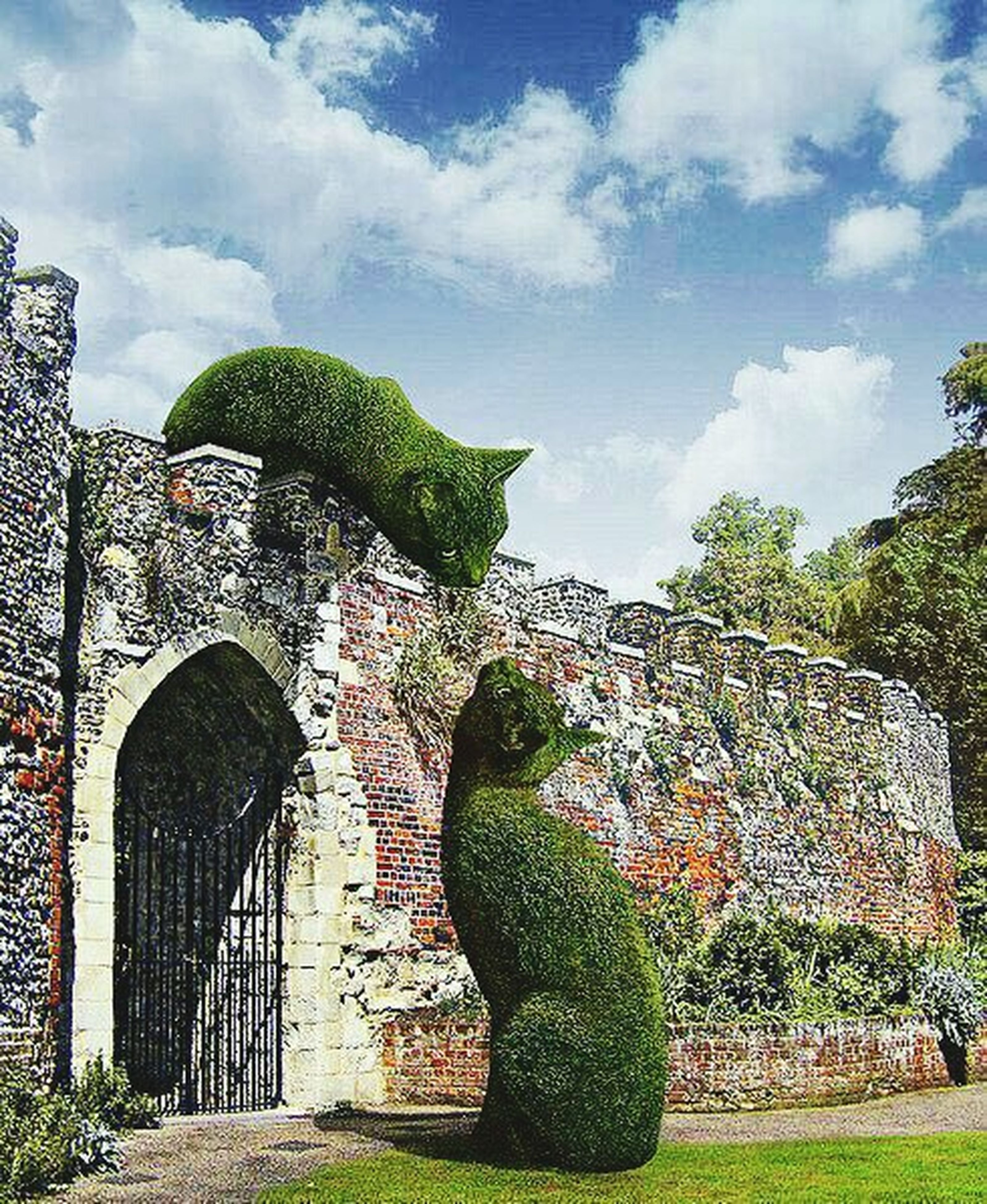 built structure, architecture, building exterior, sky, tree, grass, cloud - sky, stone wall, old, green color, plant, history, wall - building feature, day, outdoors, graffiti, abandoned, arch, cloud, weathered