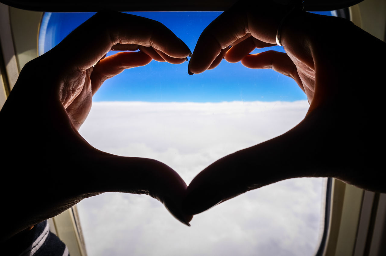 Close-up of hands forming heart against airplane window