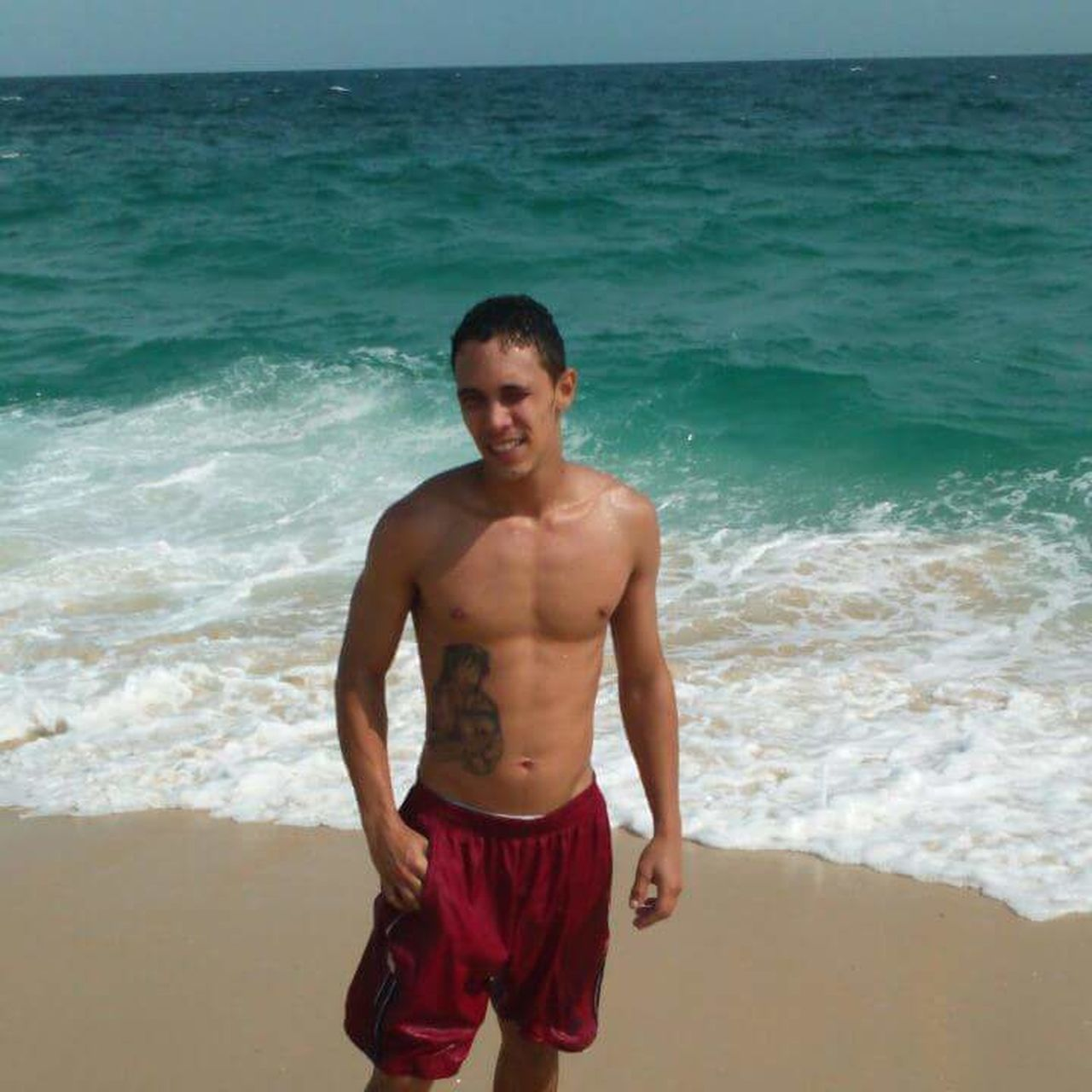 sea, shirtless, beach, portrait, one person, looking at camera, standing, wave, vacations, sand, one man only, front view, smiling, day, outdoors, nature, sport, only men, water, muscular build, young adult, people, adult, adults only
