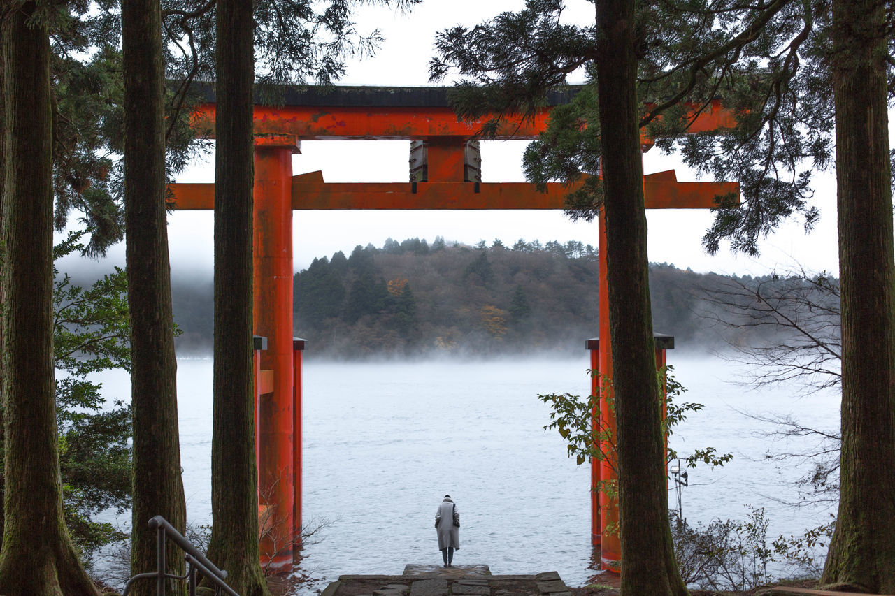 Person Standing At Lakeshore Seen Through Torii Gate