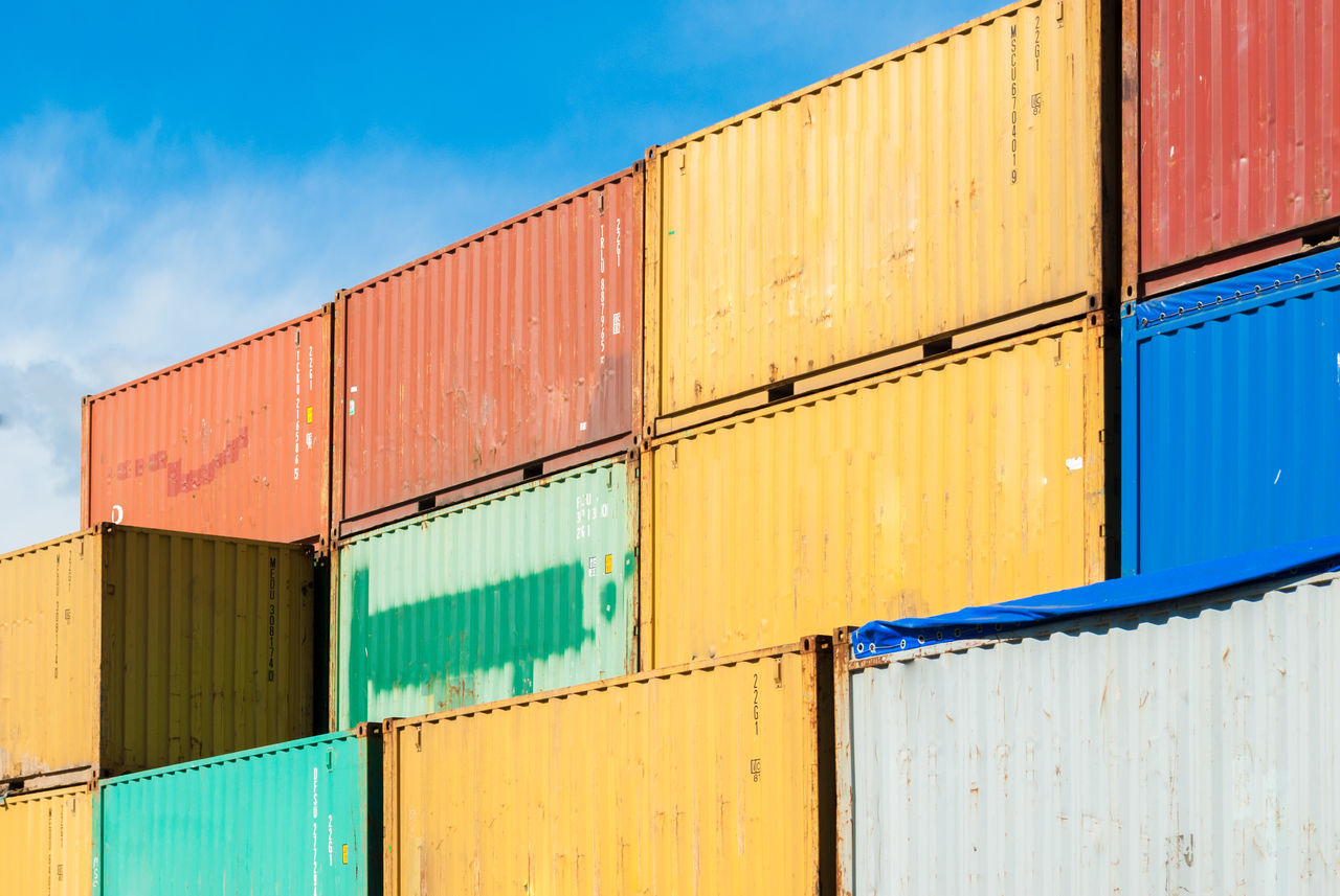 Stacked colored containers Cargo Cargo Container Colored Container Containers Day Export Freight Freight Transportation Harbor Harbour Import Industry Outdoors Port Shipping  Shipping  Sky Sunny