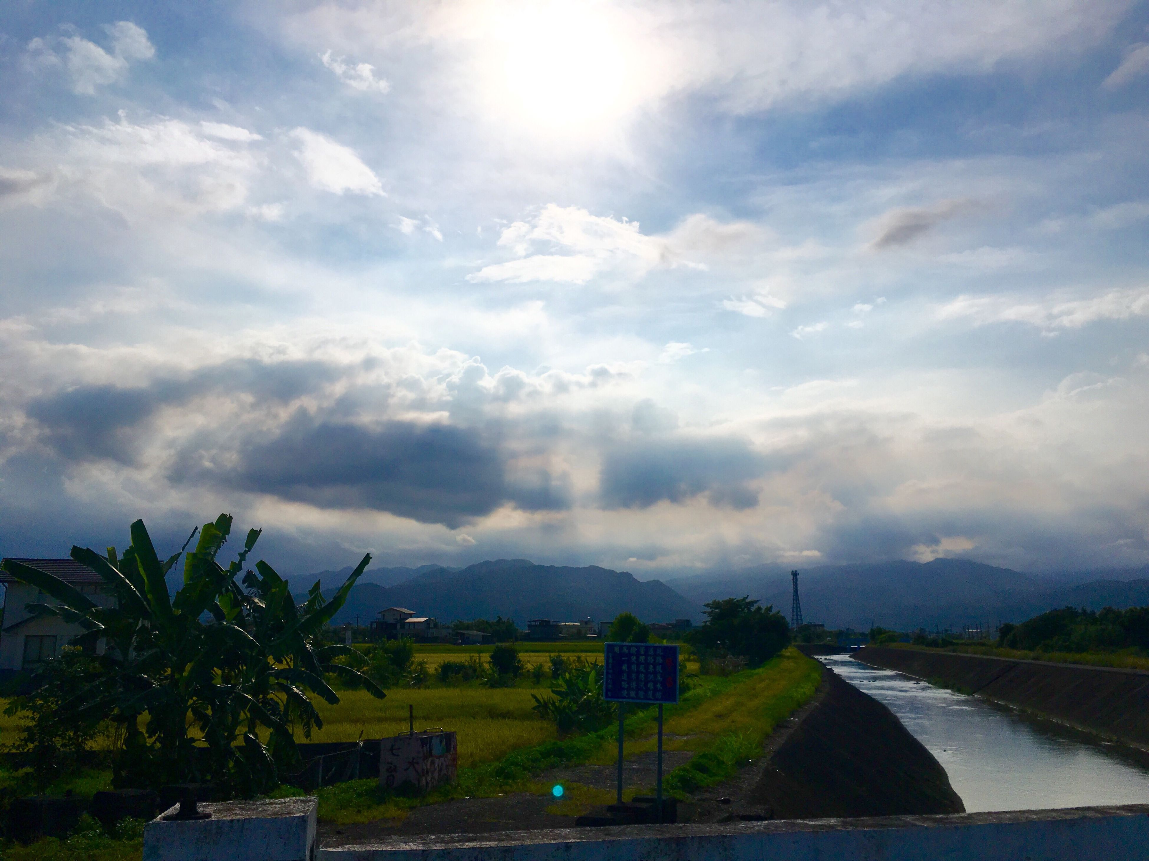 sky, cloud - sky, cloudy, landscape, tranquil scene, scenics, tranquility, beauty in nature, nature, cloud, rural scene, outdoors, no people, weather, green color, day, grass, idyllic, growth, mountain, sunbeam, overcast, non-urban scene, horizon over land, sun, remote
